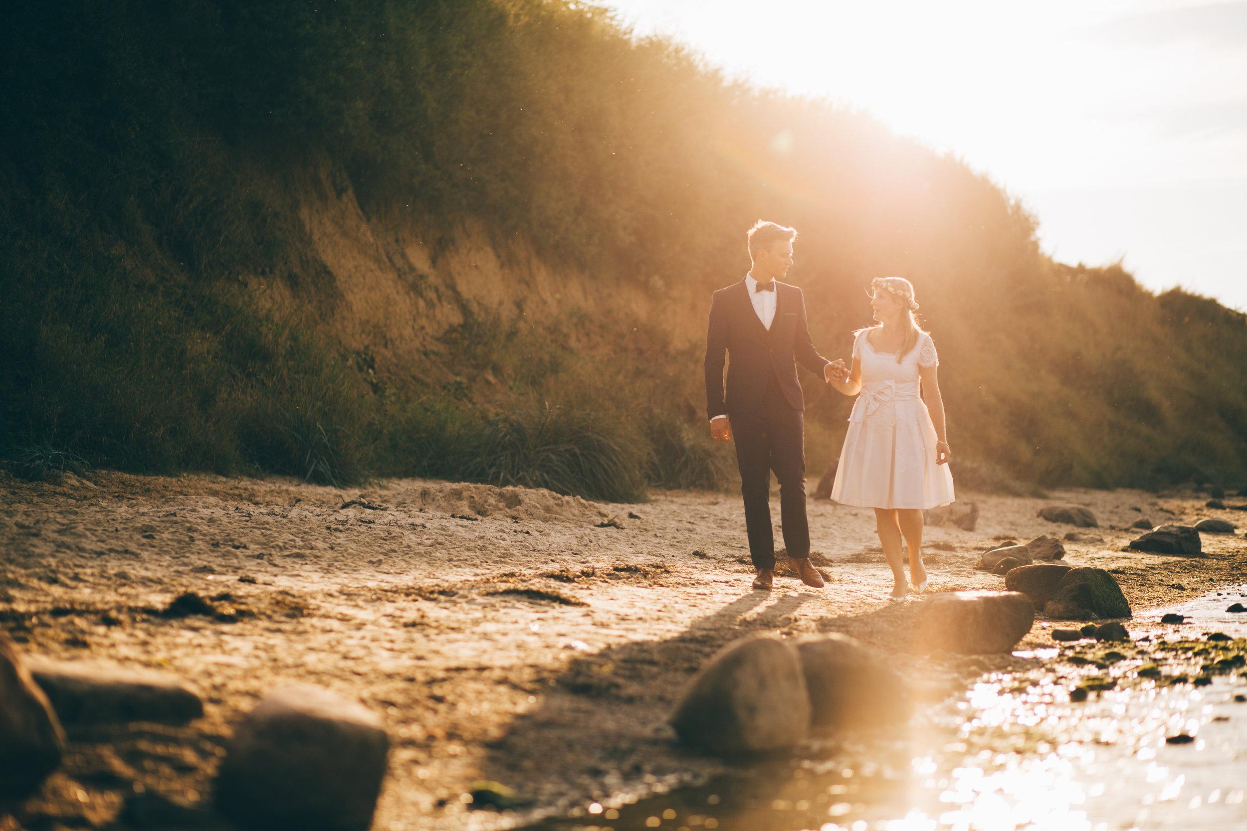 Hochzeitspaar an der Steilküste in Stein bei Kiel. Die Sonne geht unter und sie laufen Hand in Hand am Wasser entlang. Foto von Fotograf Phil Schreyer