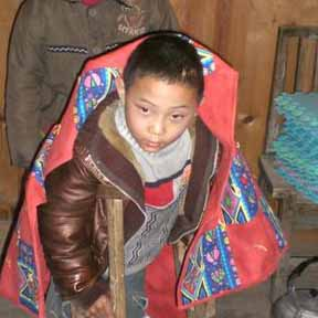 Young boy cuddled up with quilt