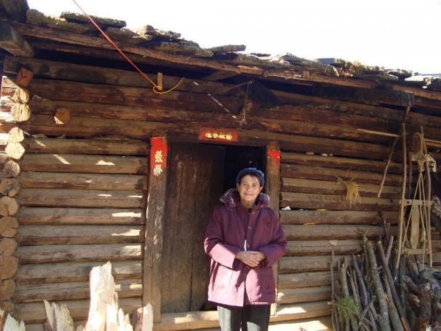 Lisu women outside her home wearing new winter coat