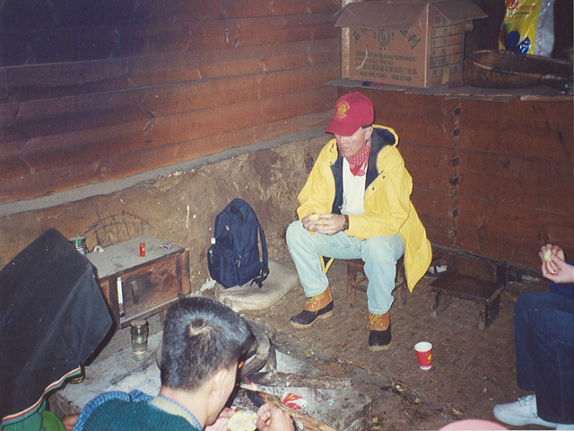 Brad eating a fire baked potato in Yi village home