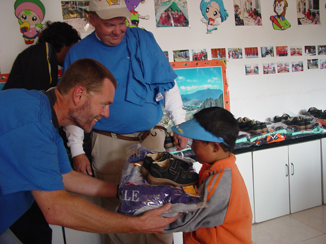 Scott handing out clothing at orphanage in Tibet