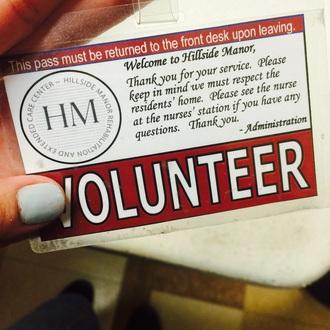 A Volunteer Proudly Displays their Volunteer Badge