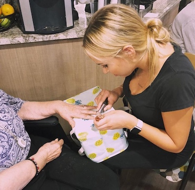 Kristina paints the nails of a senior at the center her chapter visits.