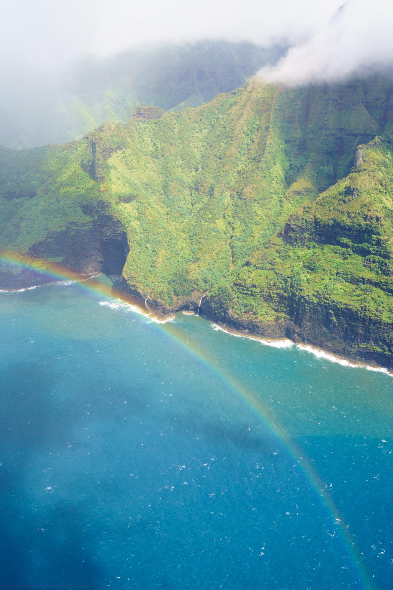 Rainbows and waterfall views along the Na Pali Coast Kauai   Never Settle Travel