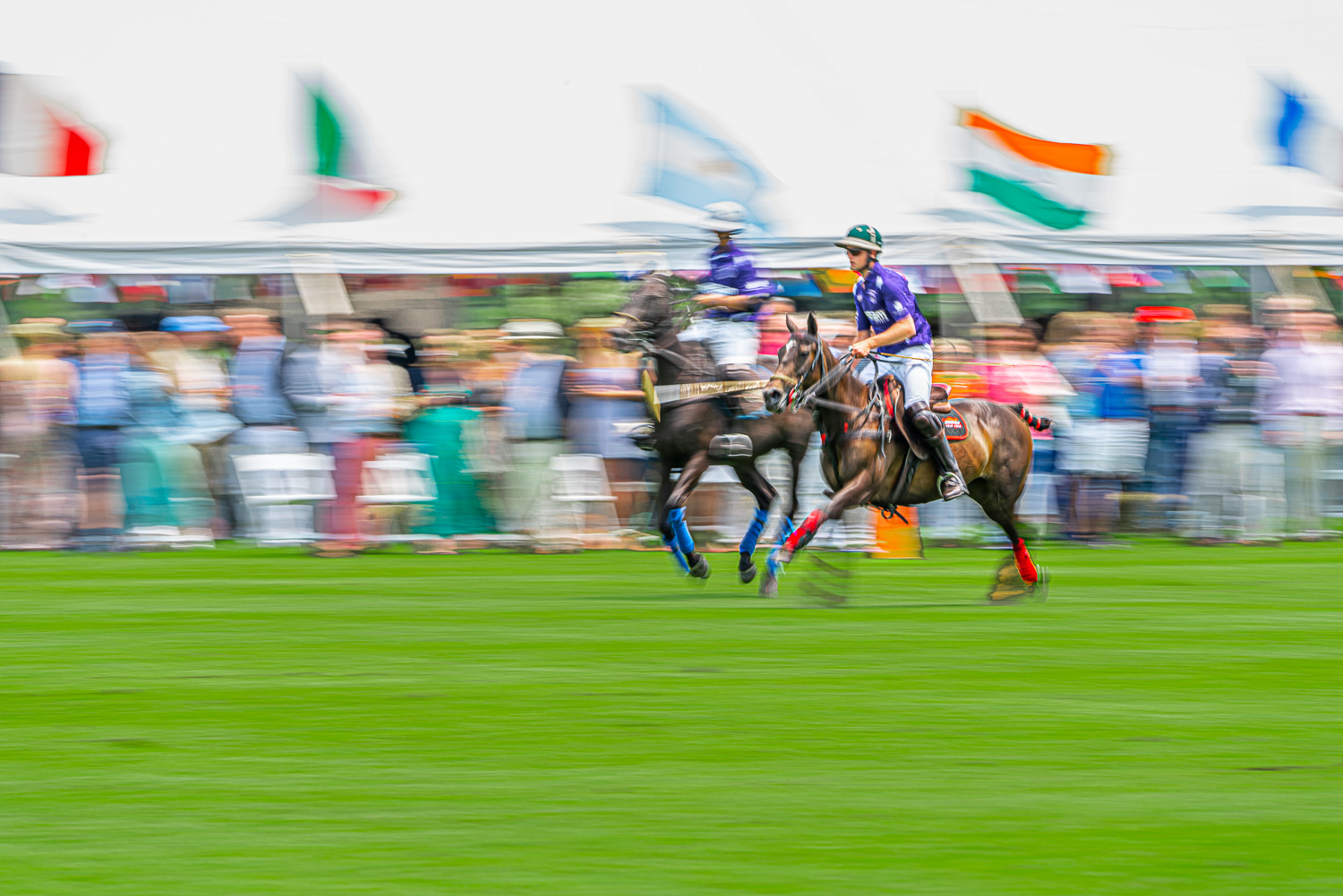 polo players battle it out in front of the grand stands at the mashomack polo club in pine plains, ny.  The action blur creats a sense of speed and movem.jpg