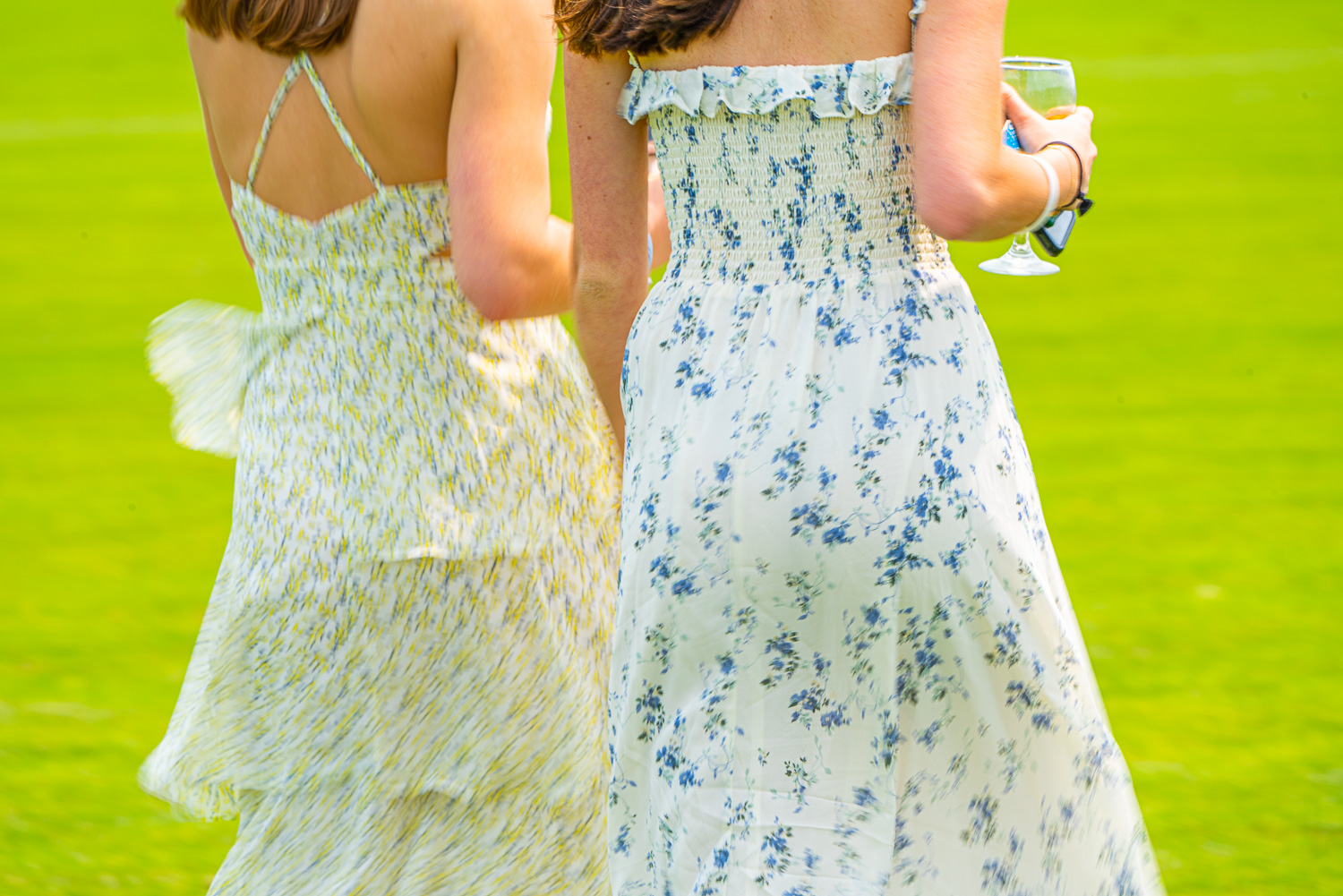 Two women dress for the occasion. Polo anyone at the Mashomack Polo Club, pine plans, ny.  The action blur creats a sense of speed and movement..jpg