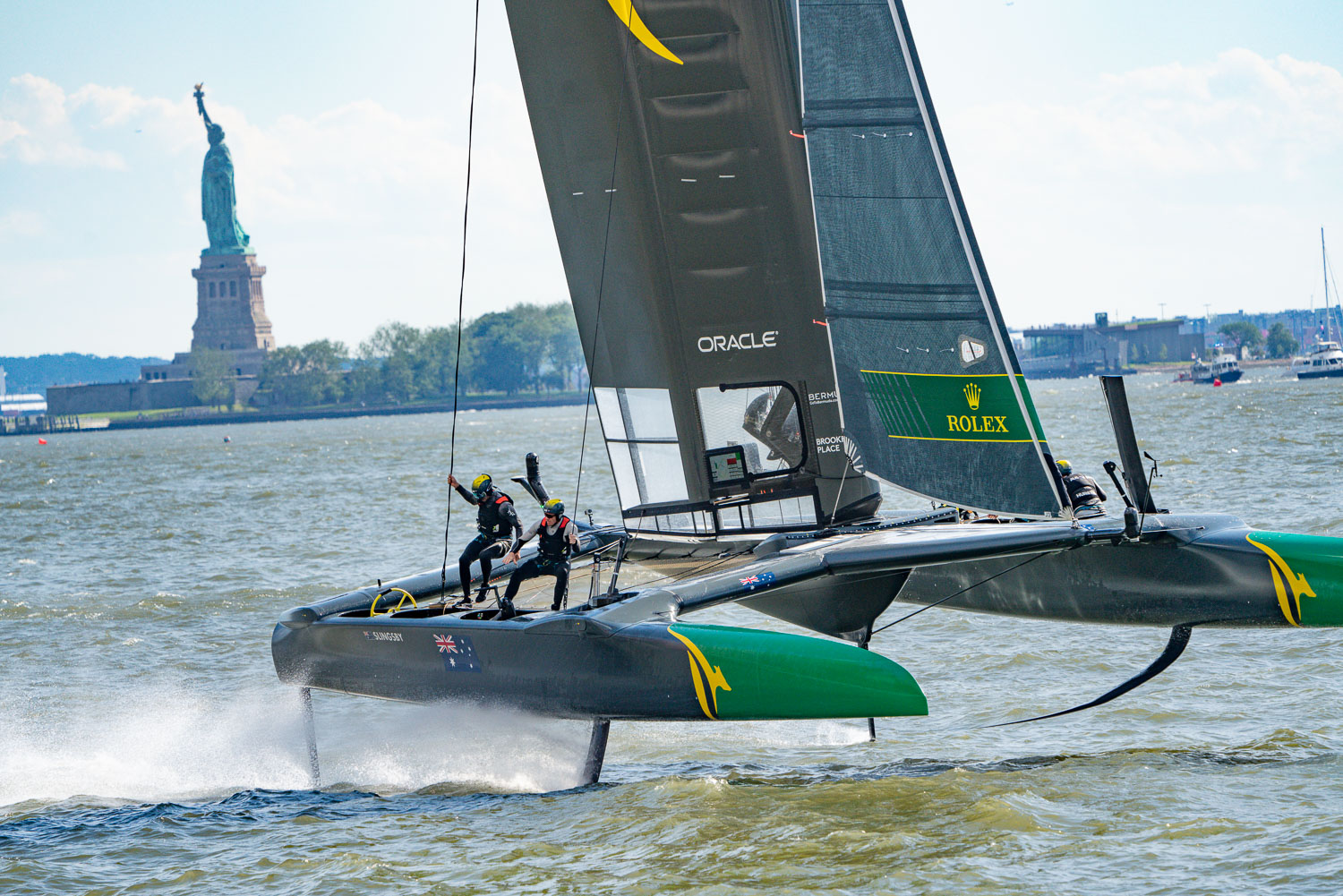 The crew of GB dancing around the deck of this Sail GP boat as shes riding her hydrofoils. The statue of liberty is in the background. Hudson river..jpg