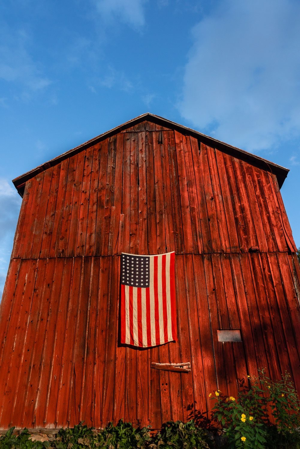 This historic barn glows in the autumn light. Its a piece of Americana with the american flag on the red barn.  johnstuartstudio-compress.jpg