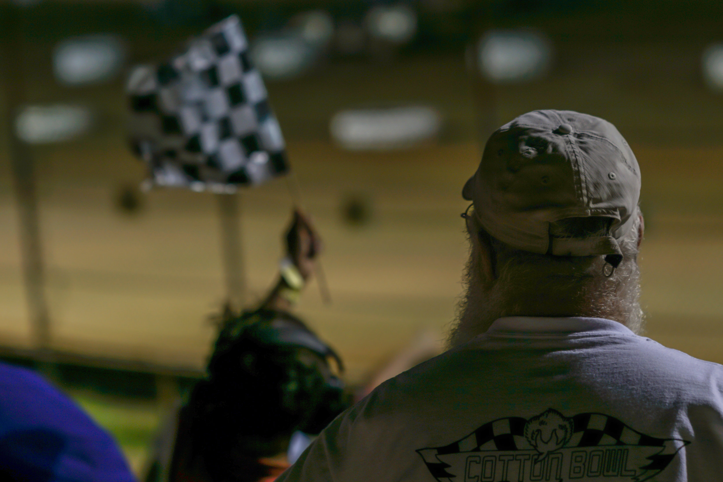 Spectator watches another fan waving the checkered flag