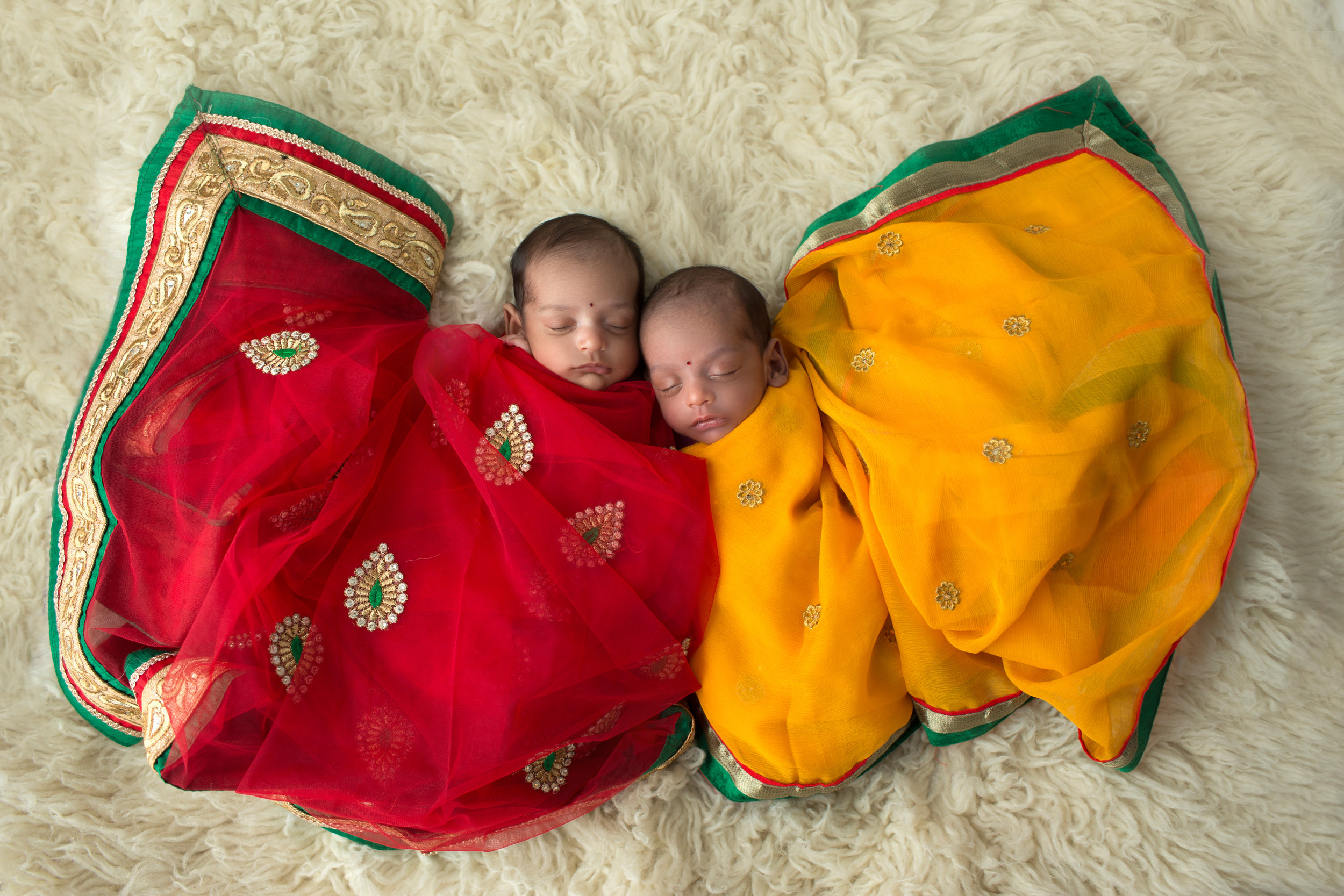 newborn twins dressed in traditional Indian wedding garb