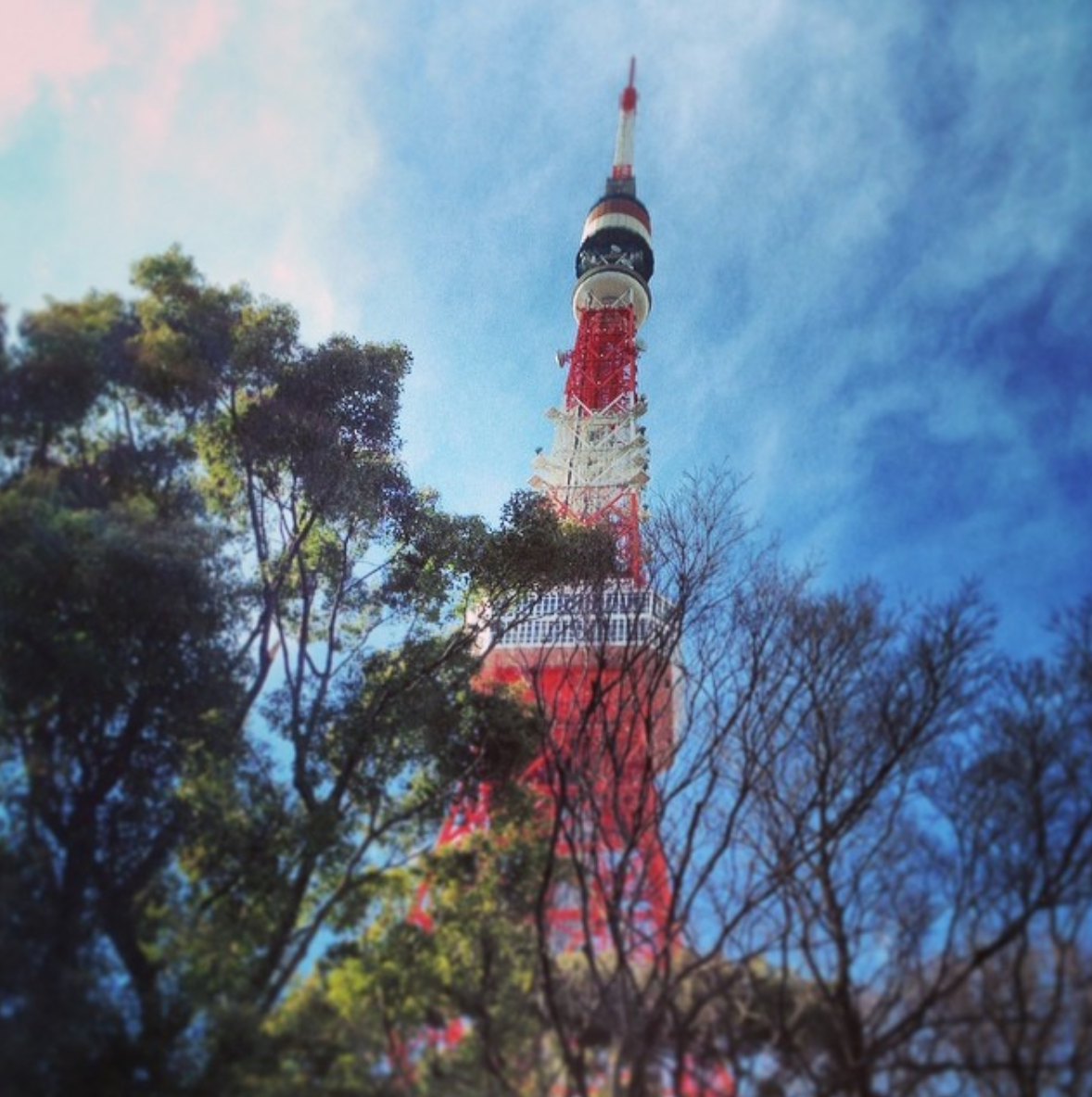 A photo taken at the base of the Tokyo Tower, which rises up red and white against a blue sky.