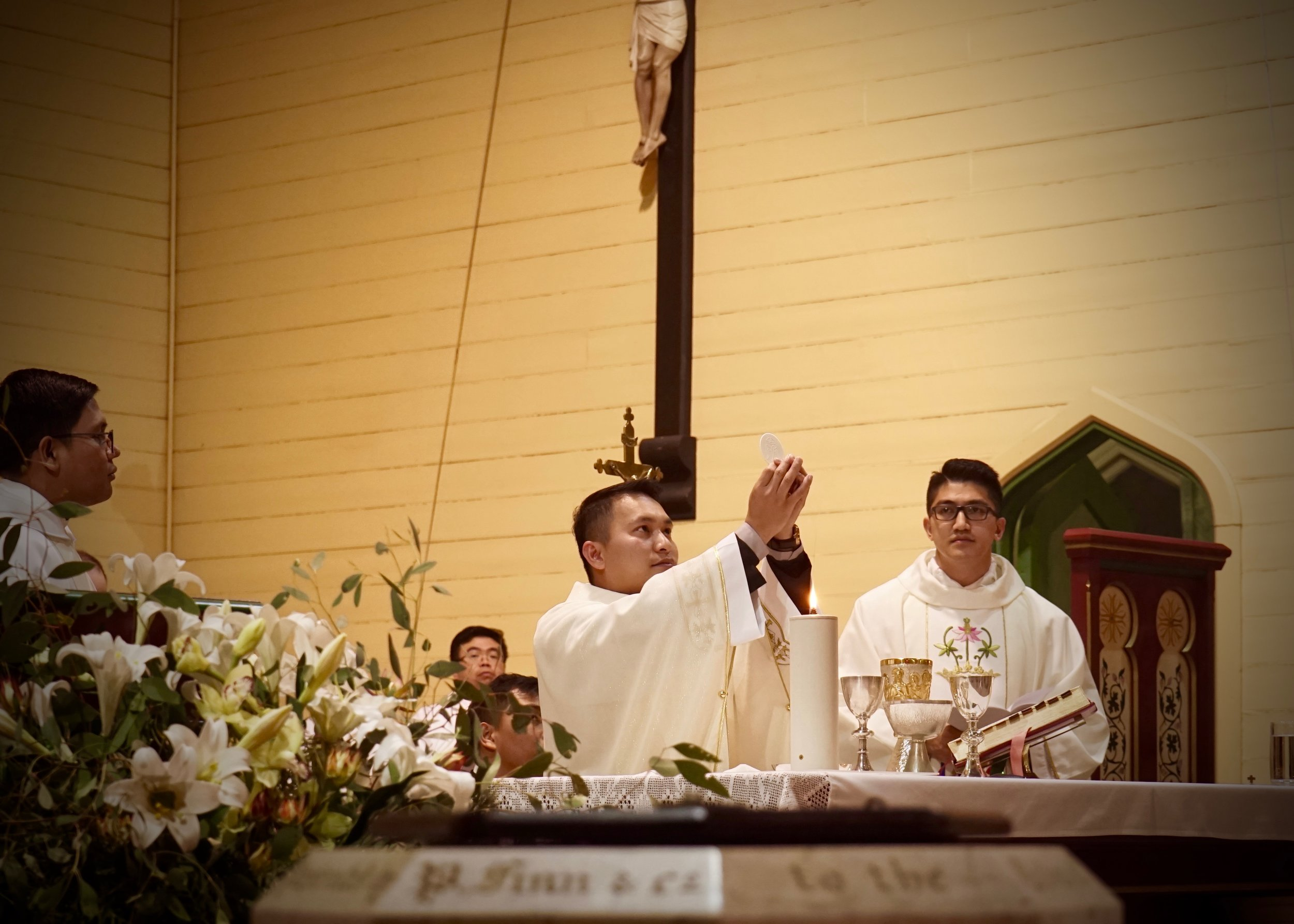 Fr Dean Bongat consecrates the bread into the Body of Christ during Mass for the first time.