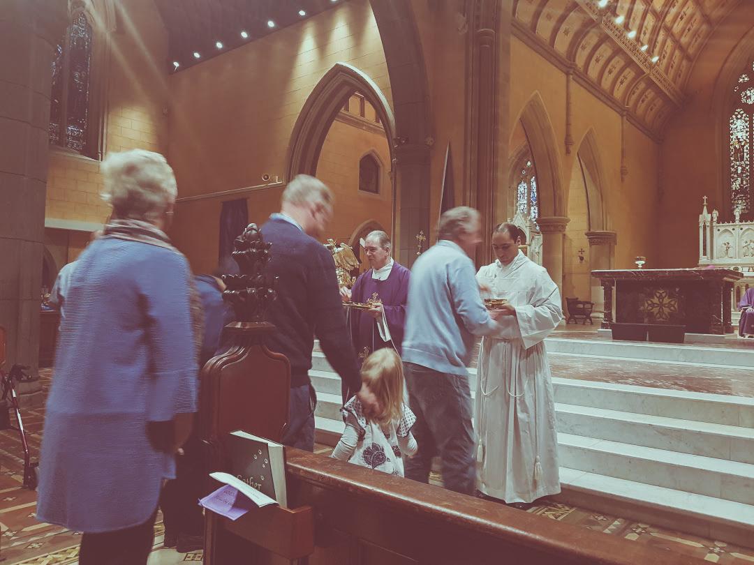 Matthew ministering Holy Communion with Bishop Paul Bird, Bishop of Ballarat.