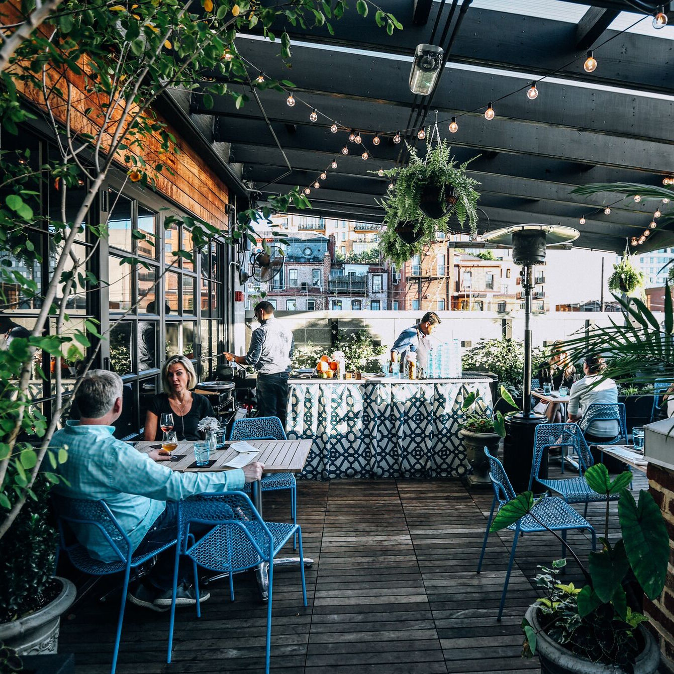 Our  Punch Garden  is outside with a garden backdrop and features creative punches and drinks alongside small bites and open seating at tables.
