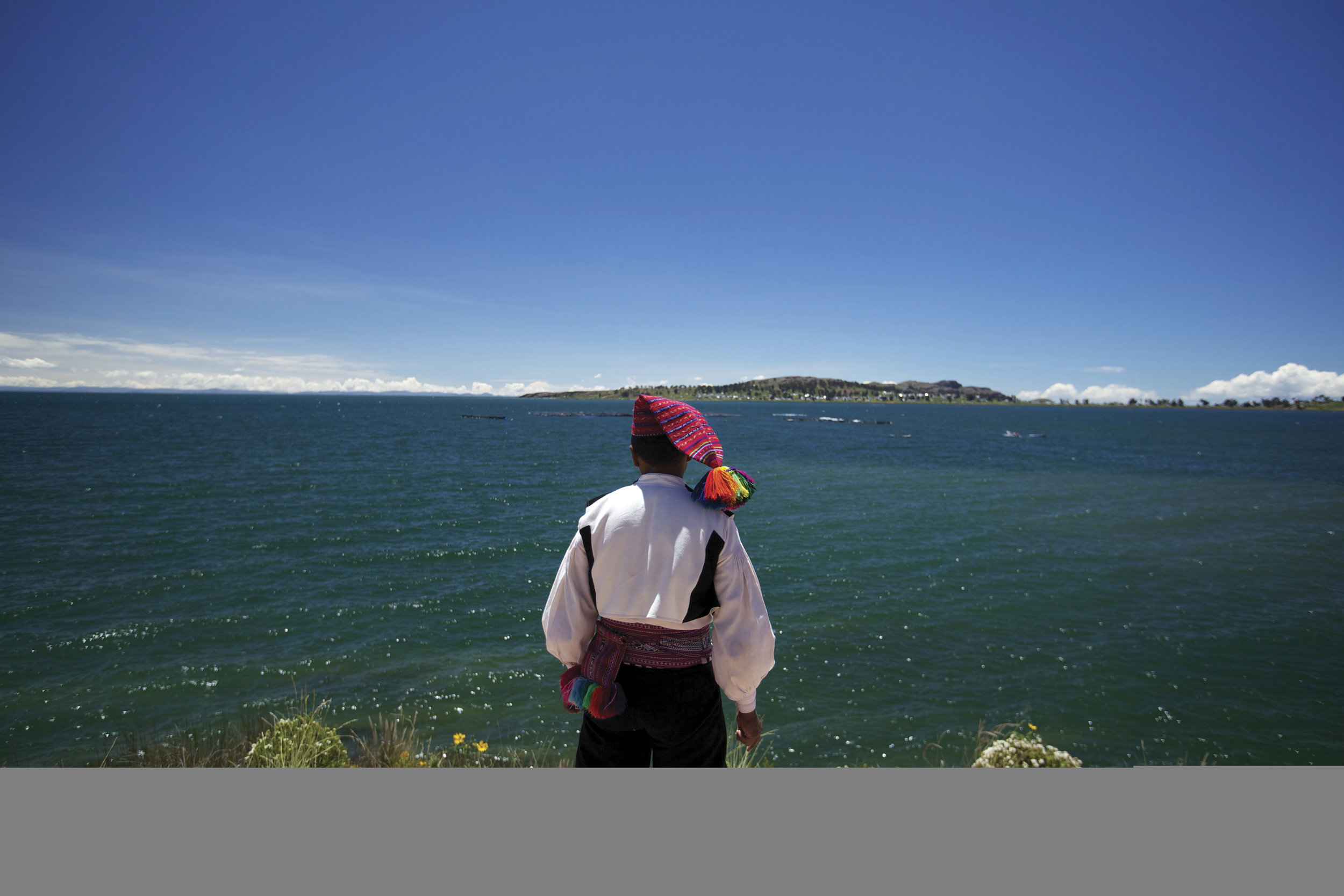 A man from Isla Taquile, in traditional dress, looks across at the sister island of Amantani.