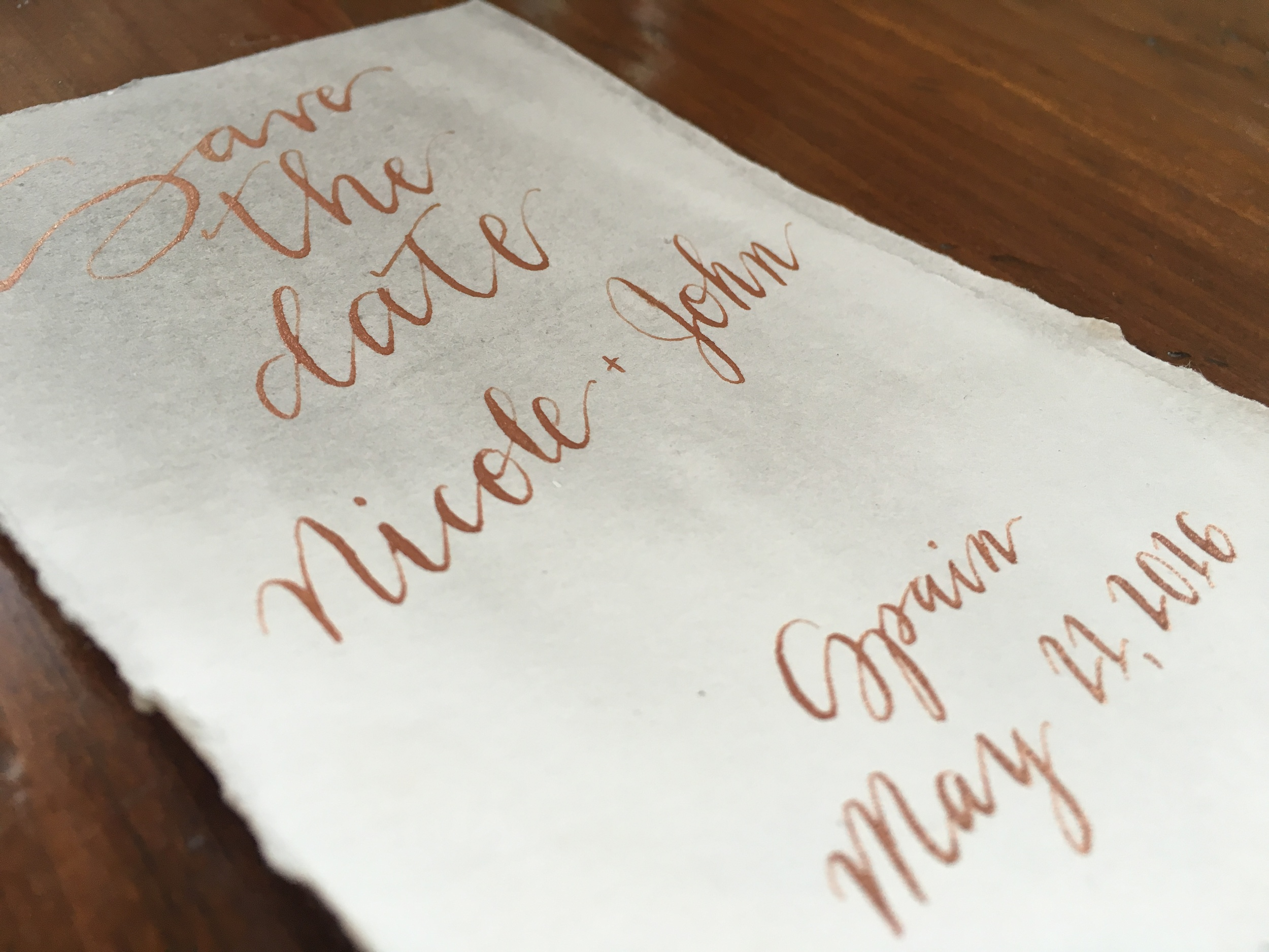 Custom lettered save the date with watercolor wash background and deckled edge for a destination wedding in Spain