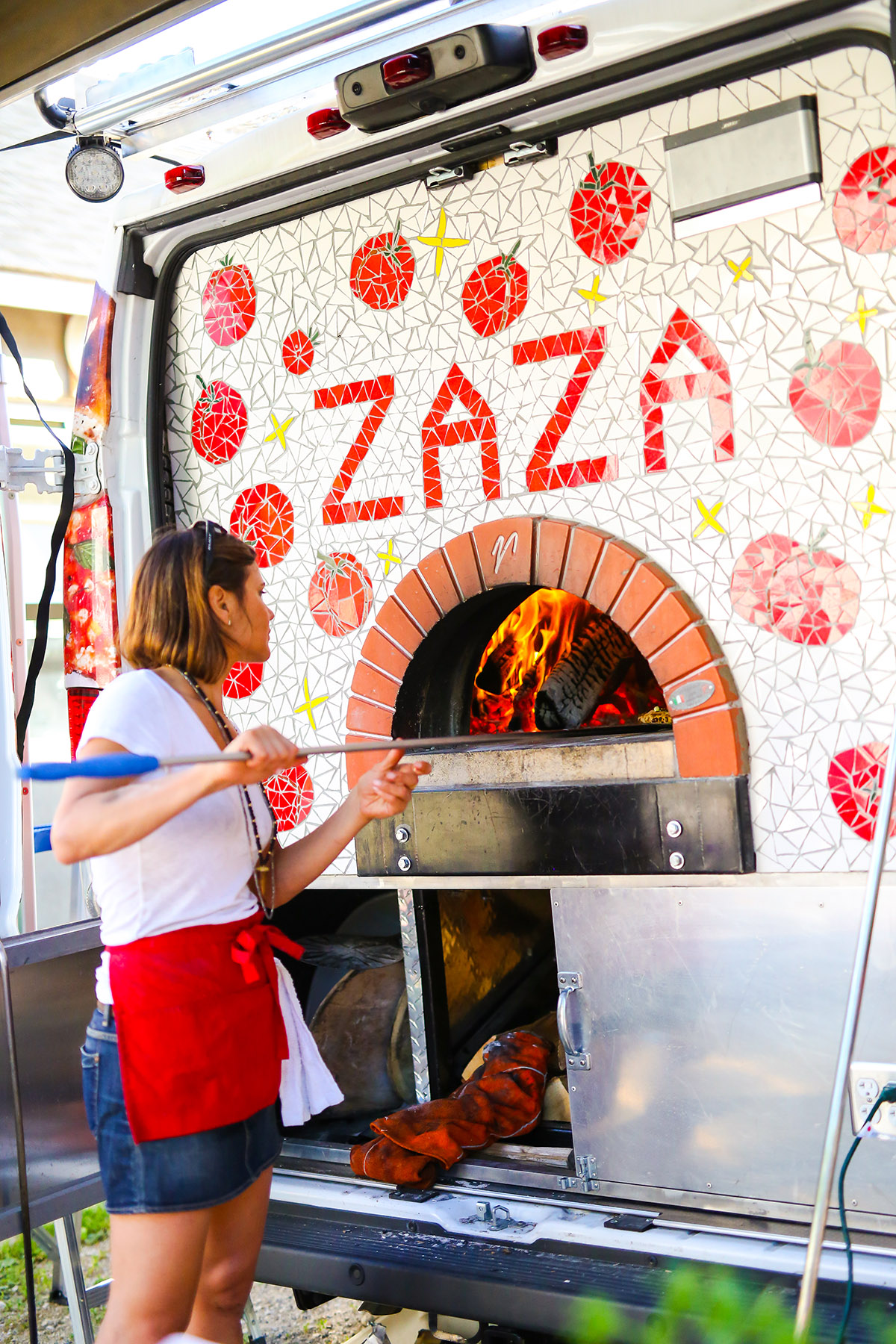 The real Zaza fishing out a Perfect Zucchini Pie from the wood-fired oven. Photo credit: Daniella Allen.