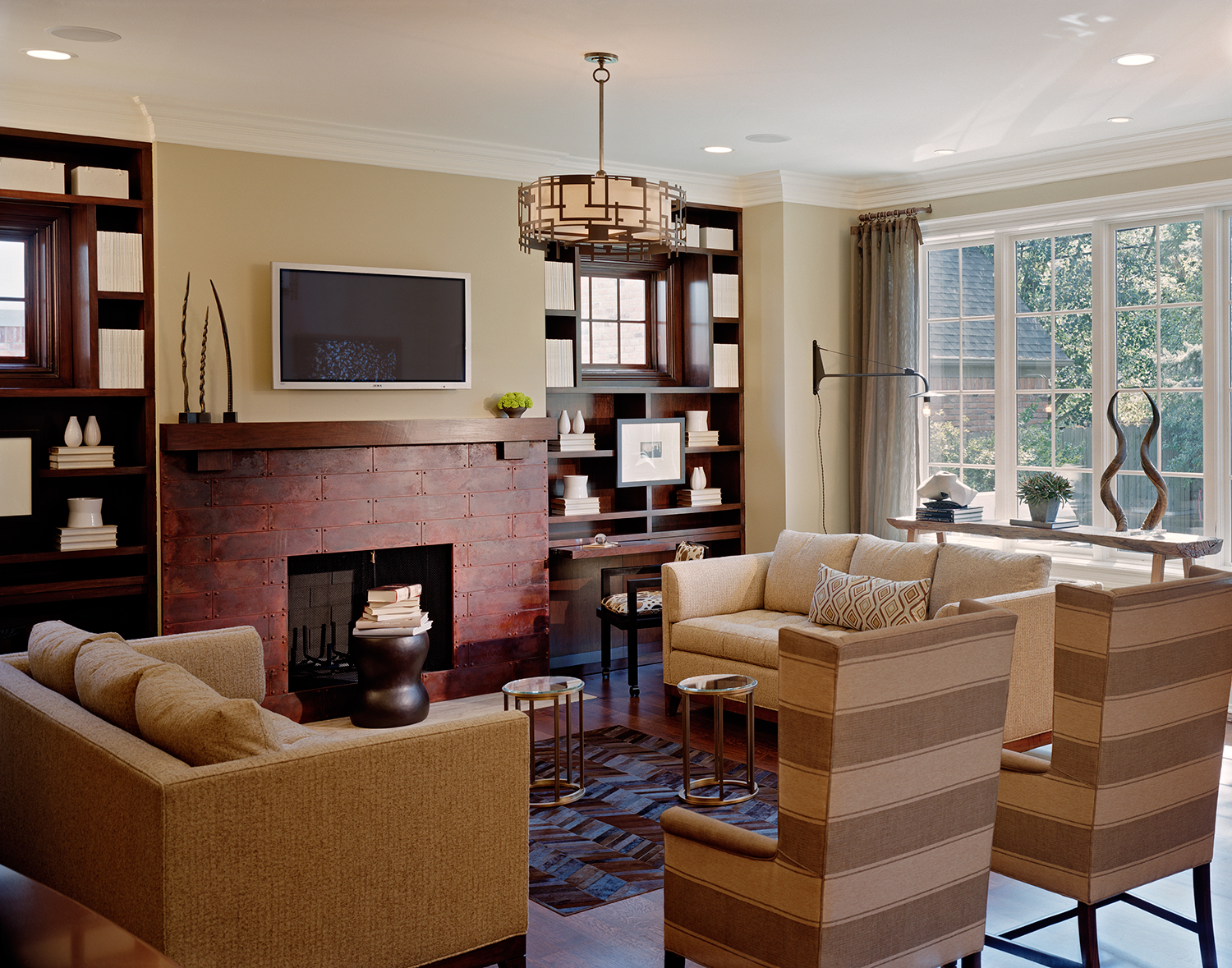 We designed the Birmingham Showhouse family room to include the characteristics of the Arts and Crafts style through the use of organic materials, with a hand-made quality. There is also slight Japanese aesthetic running through the design. It was designed to be a warm, comfortable place for the entire family to spend time in. For example, we designed the bookcases with integral, pull-out desks, allowing the room to serve many functions. The color palate is warm neutrals, with interest being added by using many textures and punches of geometric pattern. Of note, is the fireplace surround clad in patinated steel plate with rivets, the custom cow-hide herringbone rug, the drapery hardware made from copper plumbing pipe, and the antique Thai teak log trestle table. The custom ceiling light anchors the space, while the wall light swings to the desk area as needed. Photo by Justin Maconochie.
