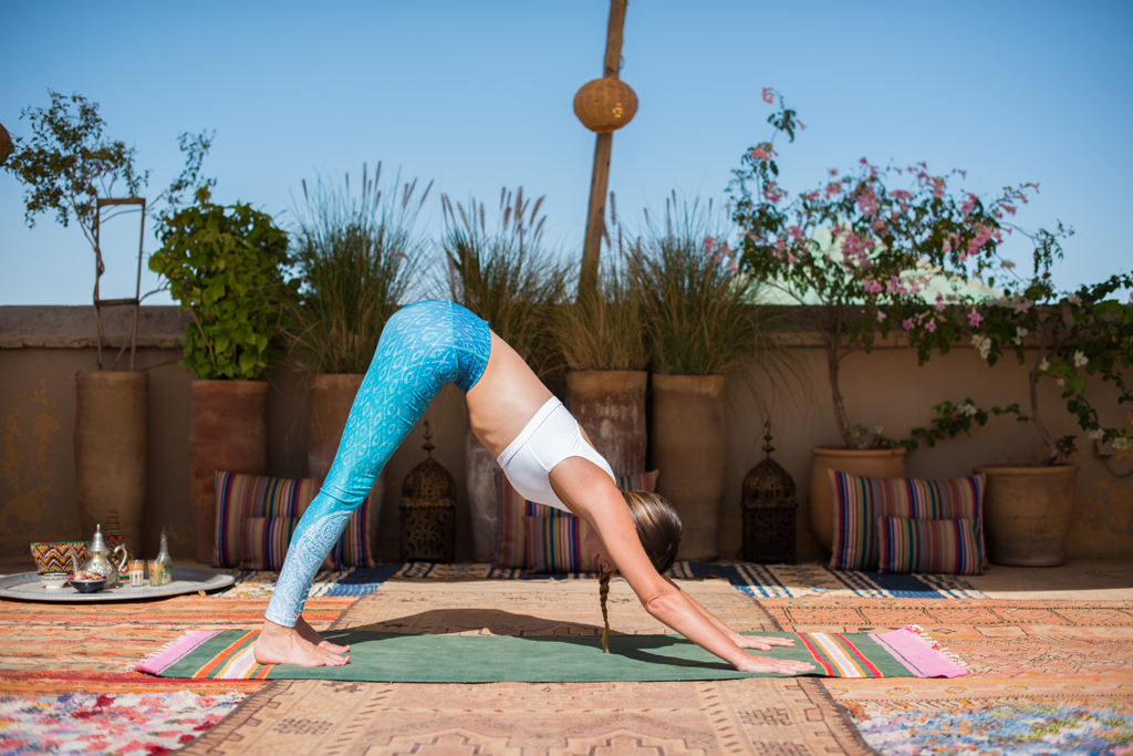 Step 1: Downward Dog - (Adho Mukha Svanasana ) This is an essential pose giving multiple benefits. Press your hands firmly into the mat and draw your shoulders away from your ears and your shoulder blades down your back. Squeeze your upper arms together as if you have a beach ball between them. Help to create more stability by drawing in the navel back towards the spine engaging the core.