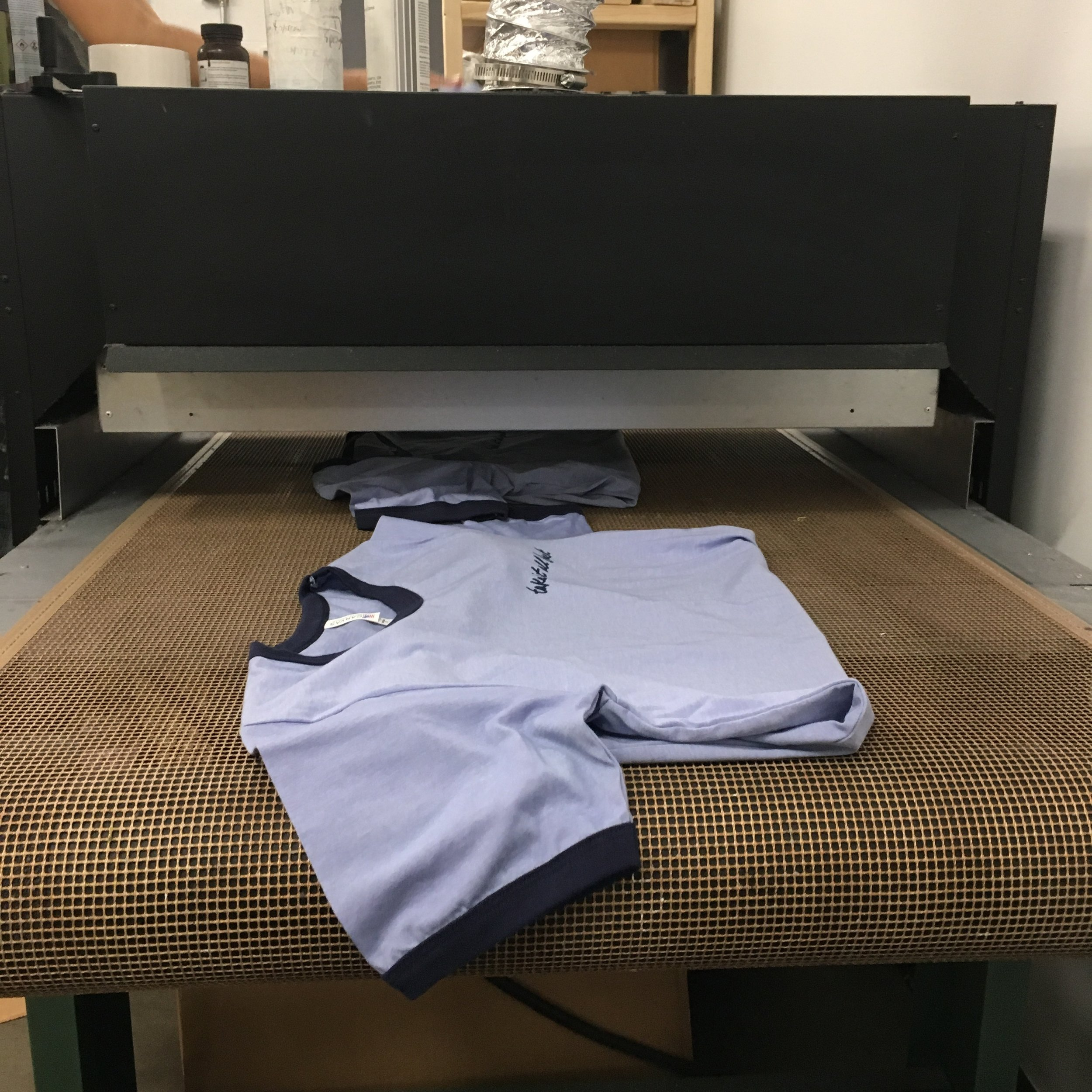 Shirts run through the dryer on a slow-moving conveyor belt.