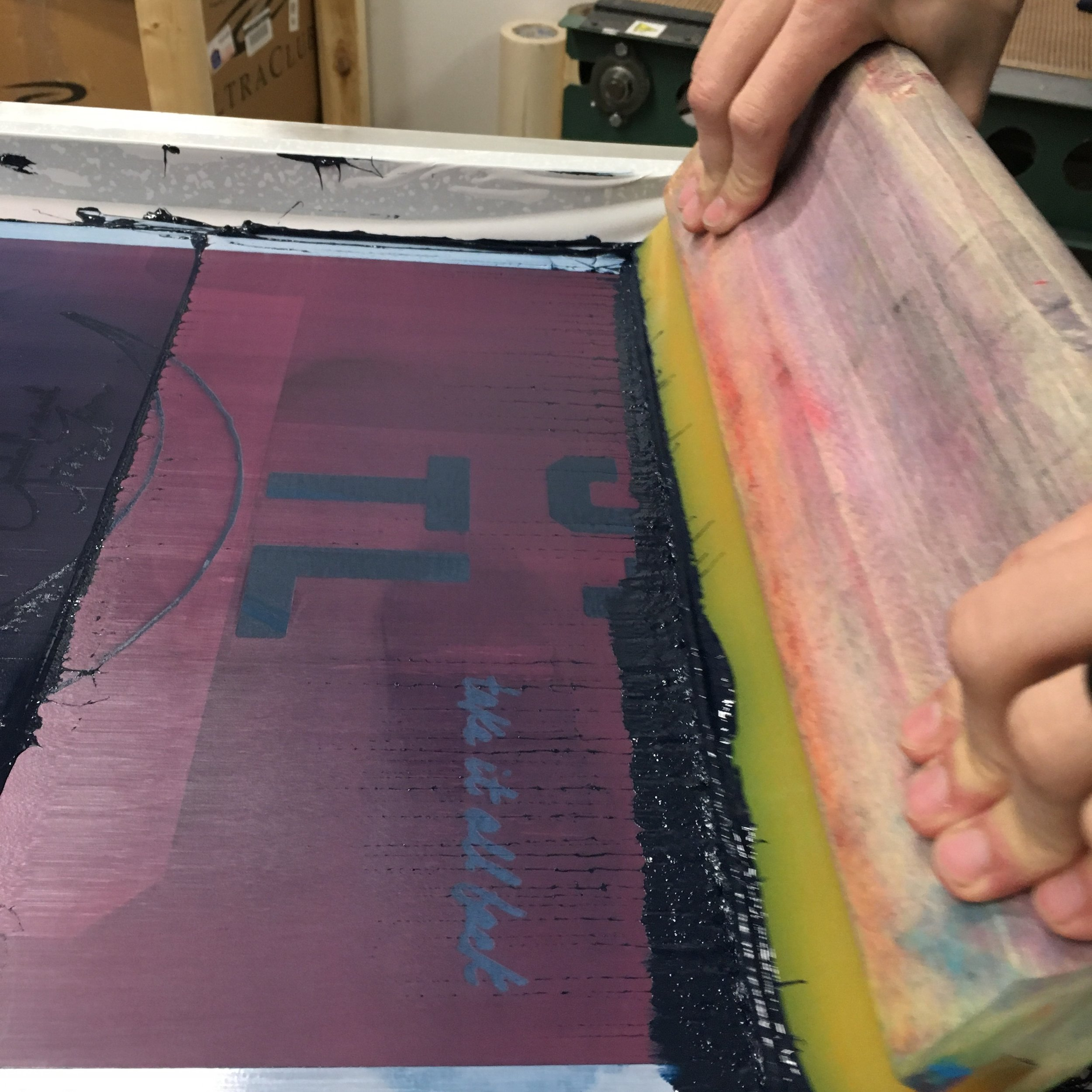 The squeegee presses the plastisol ink through the design positive and onto the t-shirt.