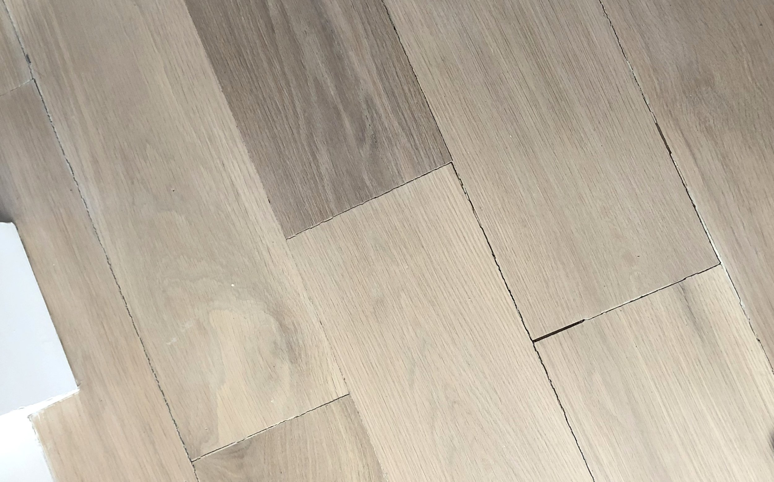 Here you can see wide plank White Oak flooring that had the gaps filled with wood filler (not by our team)…now the wood filler appears cracked and jagged in the gaps, which in my opinion looks worse than just a gap.