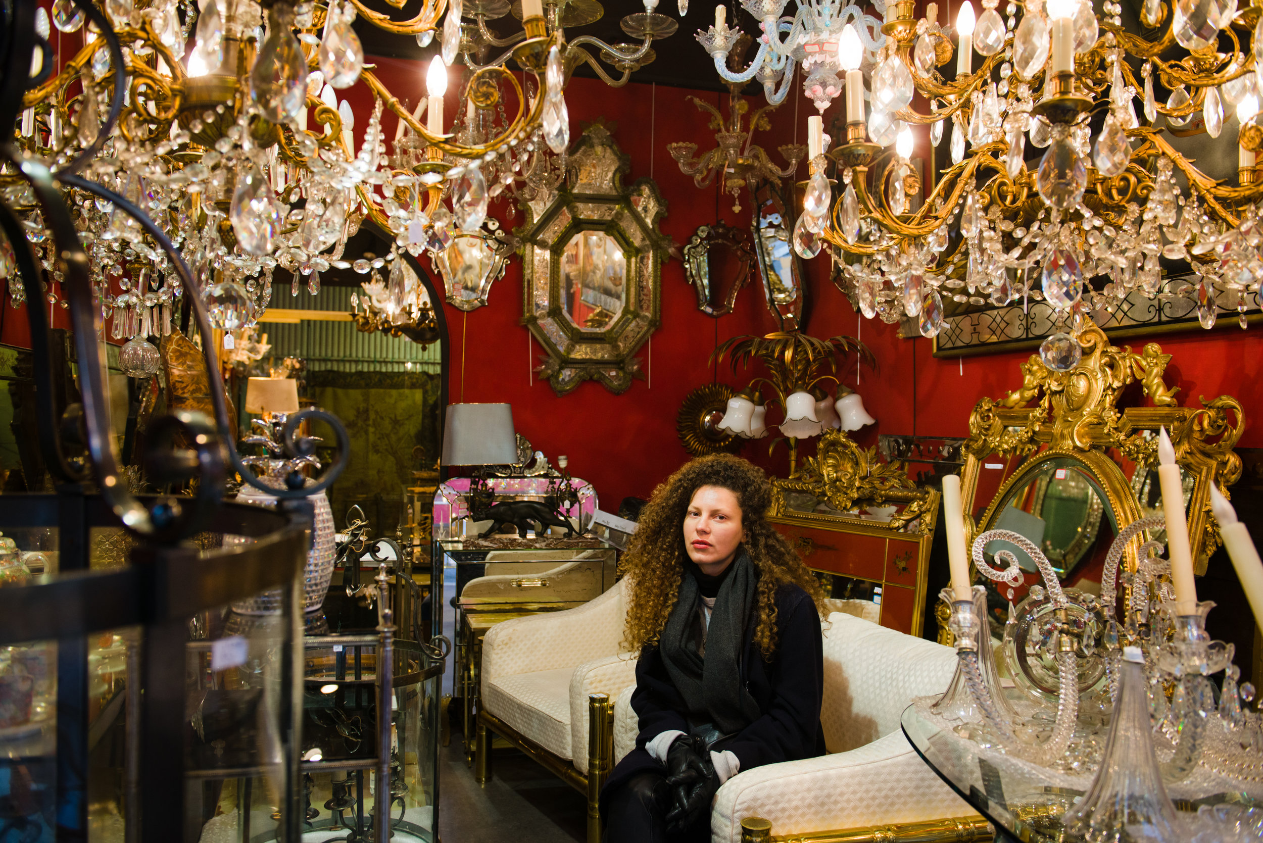 The subject is framed by the bric-a-brac of the store, in the Marché Aux Puces in Paris. Photo by William Lounsbury.
