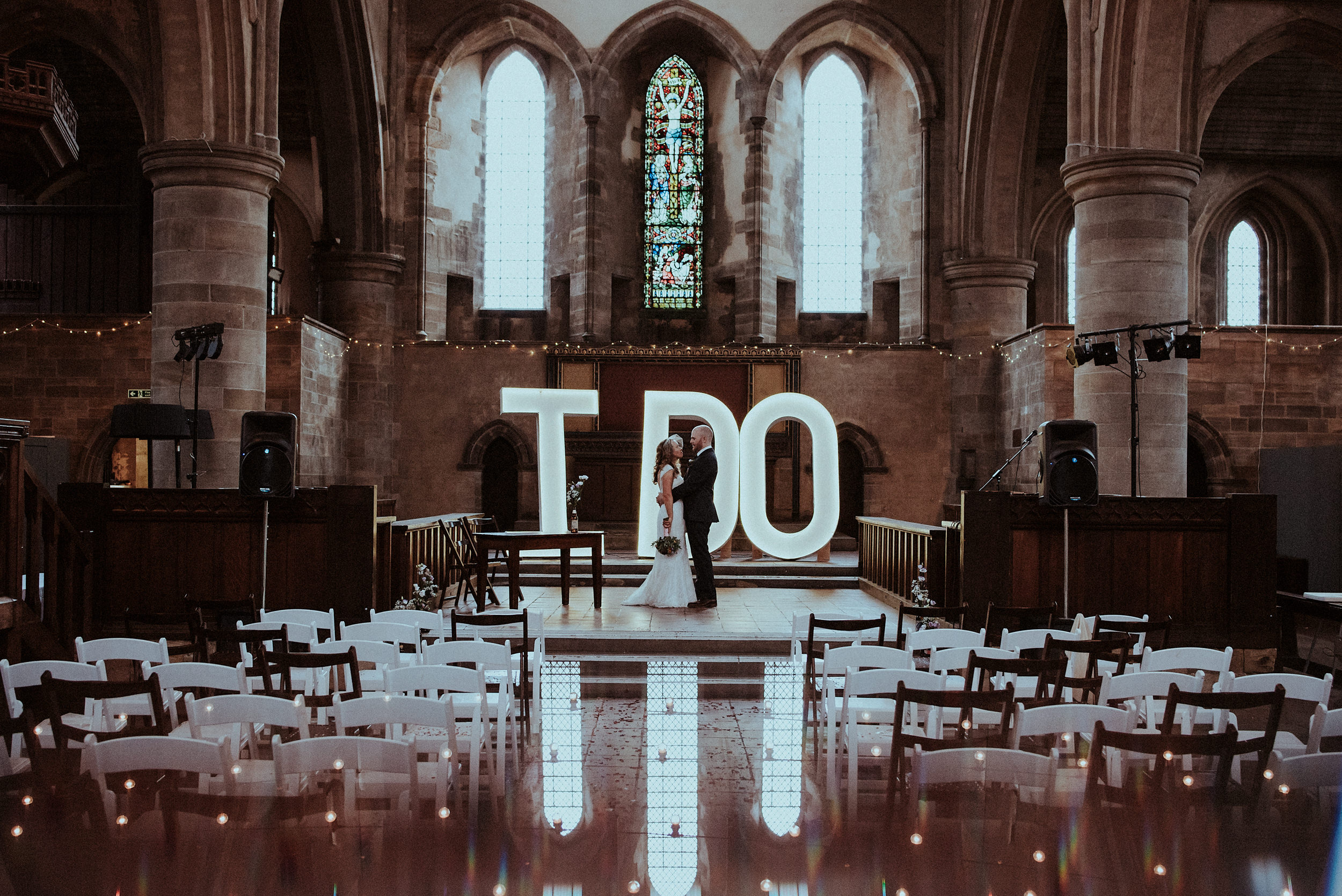 A wedding in the famous re purposed church The Left Bank Leeds. Stained glass & light up letters frame one of the most picturesque alternative wedding venues. Featured on Junebug Weddings.