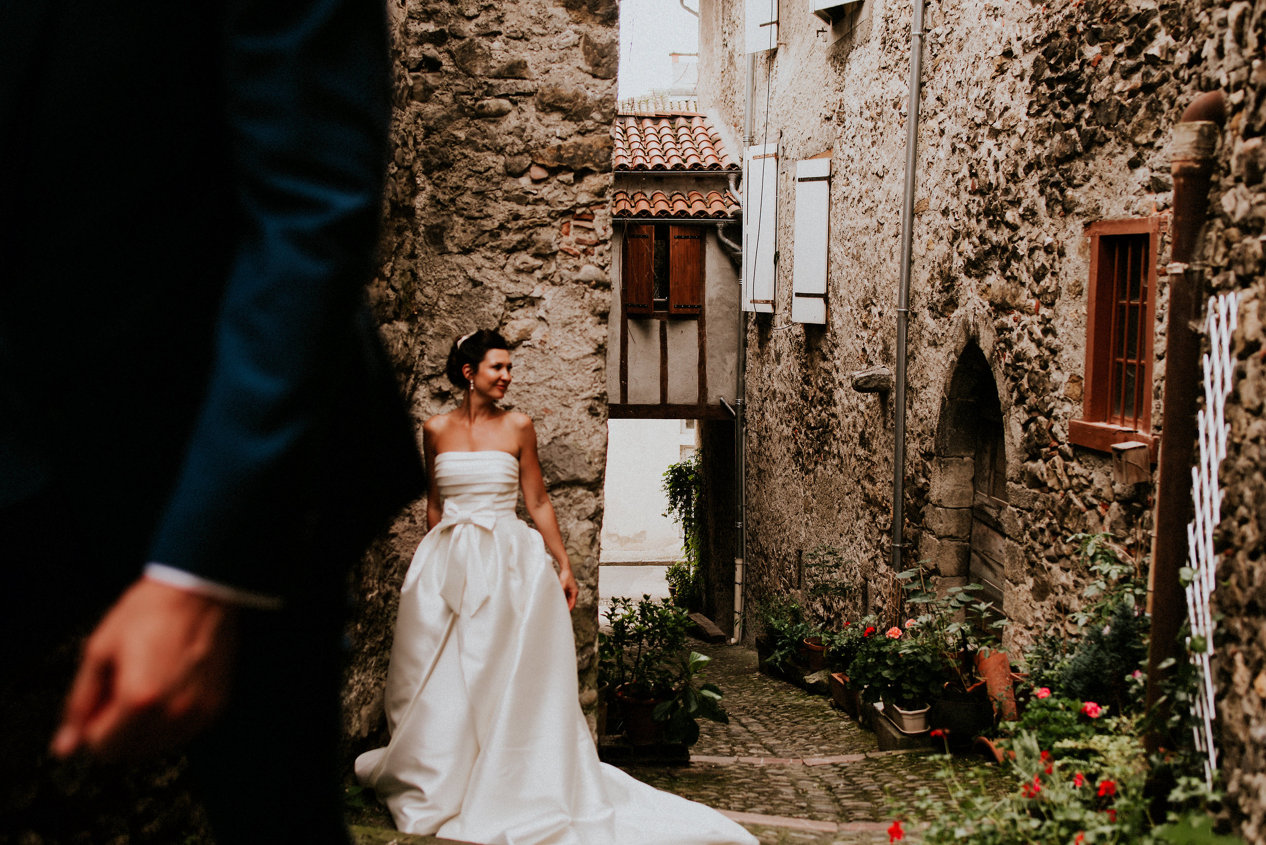 A hand fasting ceremony overlooking the Pyrenees mountains. The modern epic grandeur of Chateau St Michel. Colours collide with picturesque postcard scenes in this St Lizier  France wedding.