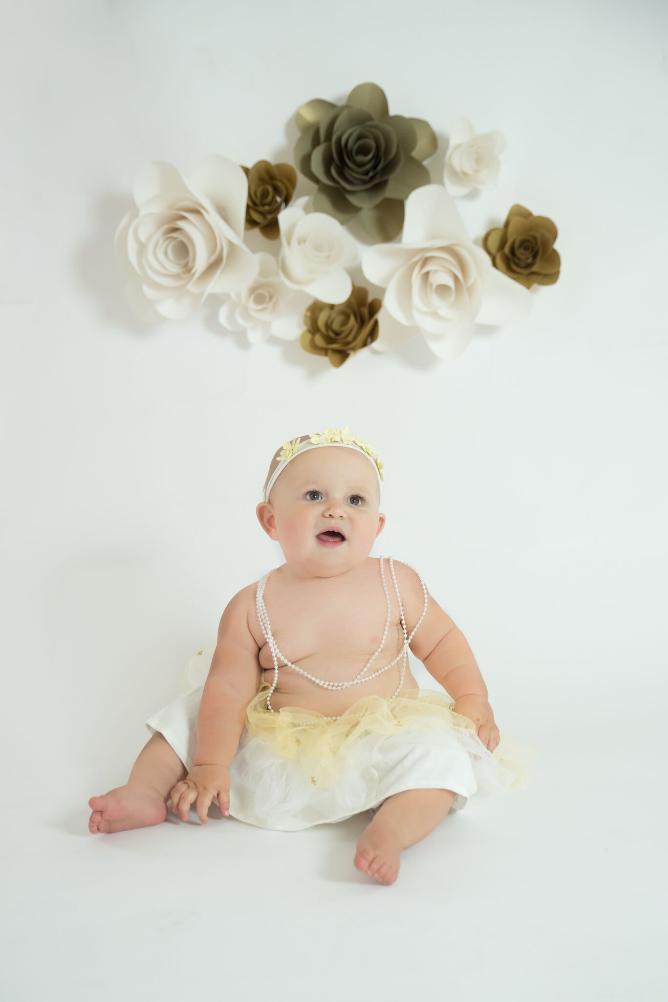Quinn is wearing a headband designed by me and the flowers on the backdrop were also created by me.  Being able to complete a setup from start to finish is very gratifying!