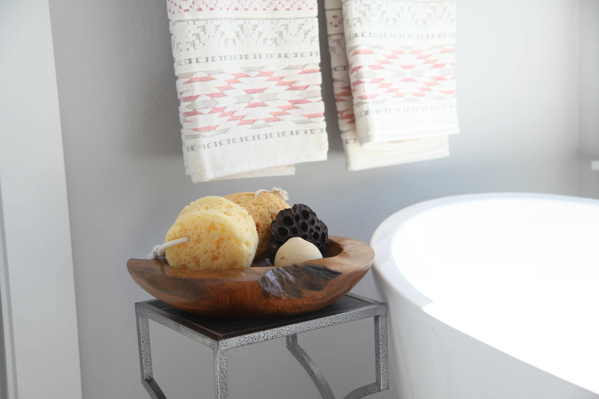 Rustic bowl with sponges next to a soaking tub is a must.