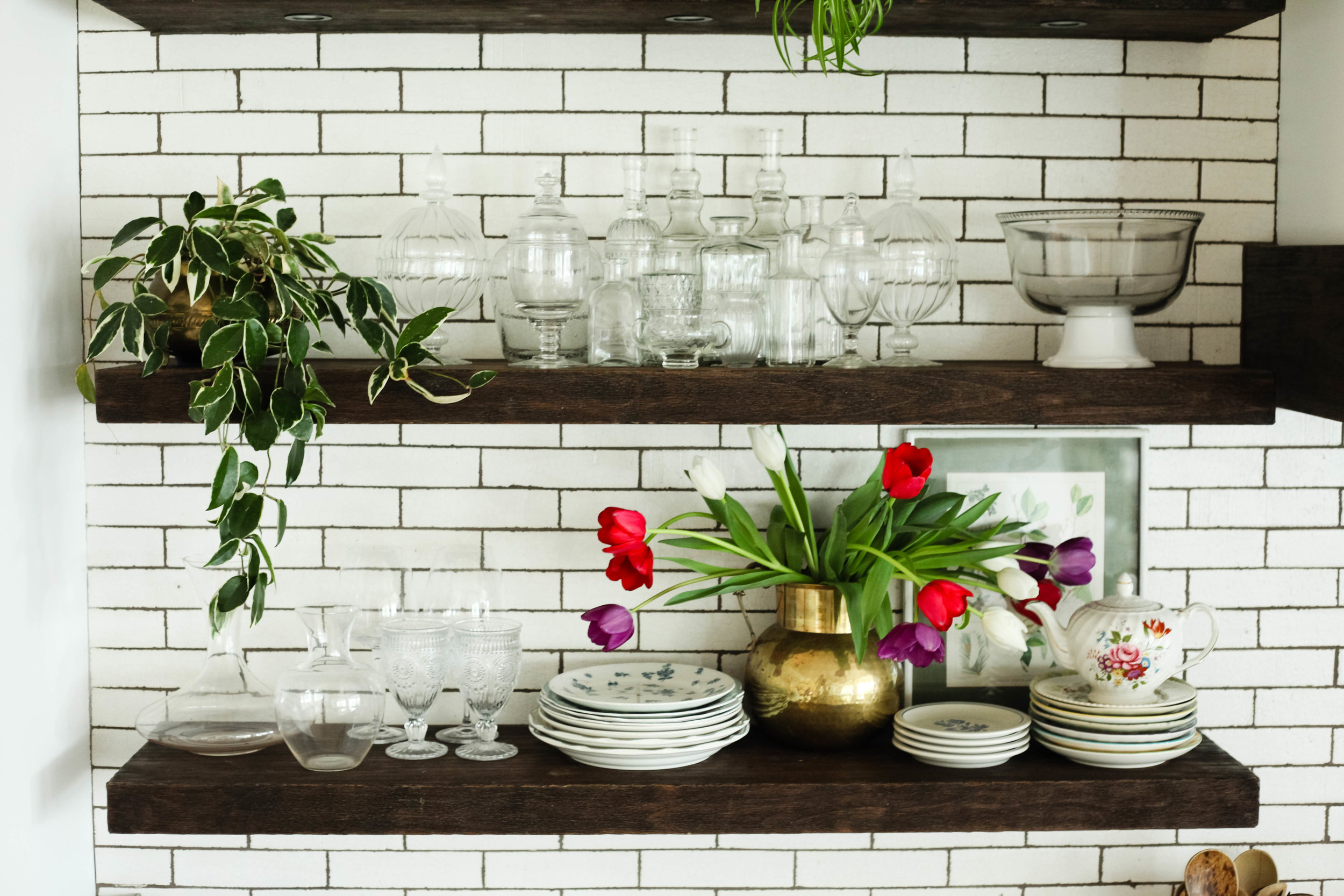 Style tip: hanging plants look intriguing next to a collection of vintage glass vases & bottles.  Style tip: Fresh flowers in a brass pot adds color and freshness to any shelf!