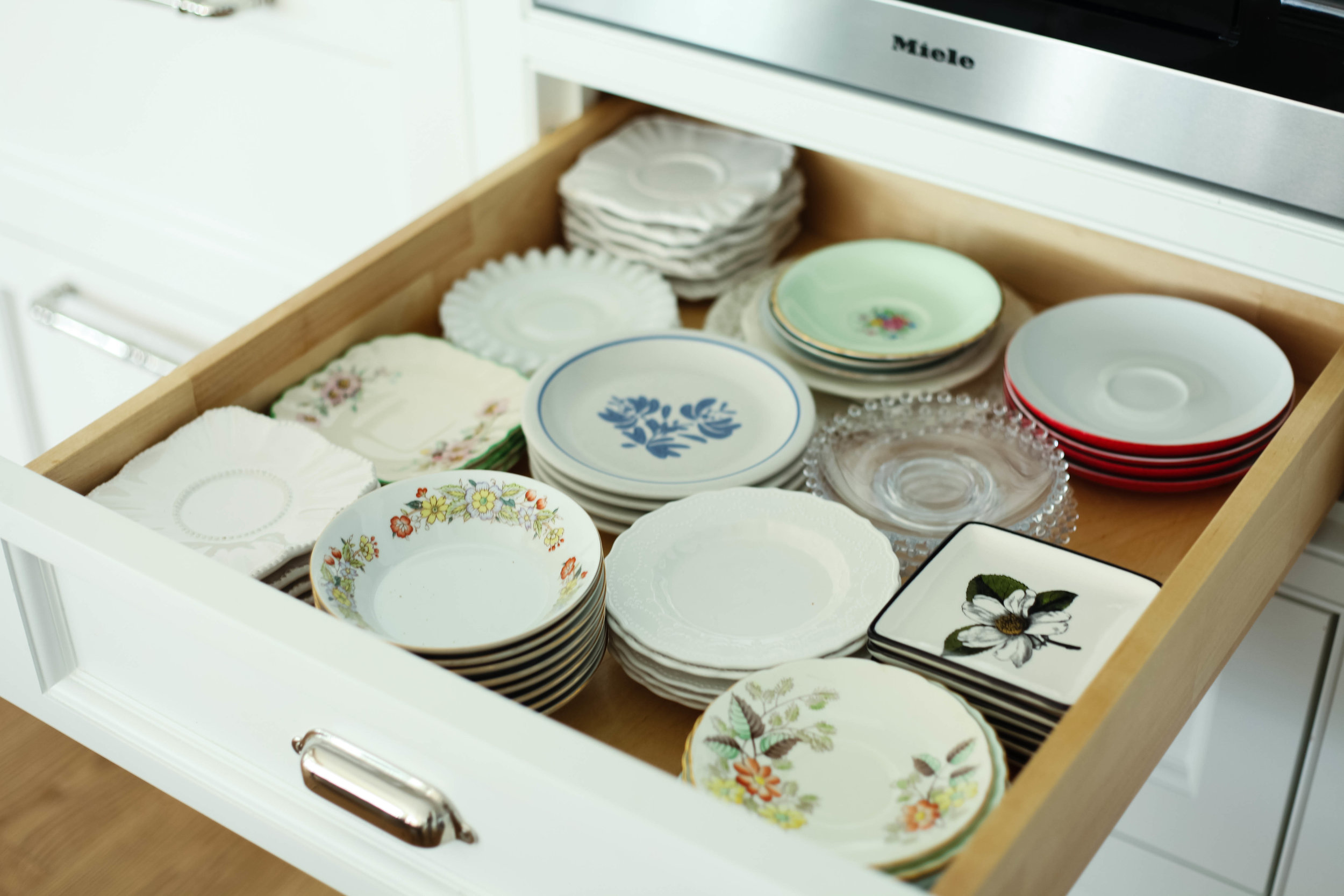 Style tip: A collection of small plates stacked inside a drawer. You can't display everything on shelves, but this way you can see what plates you have and easy to put away.