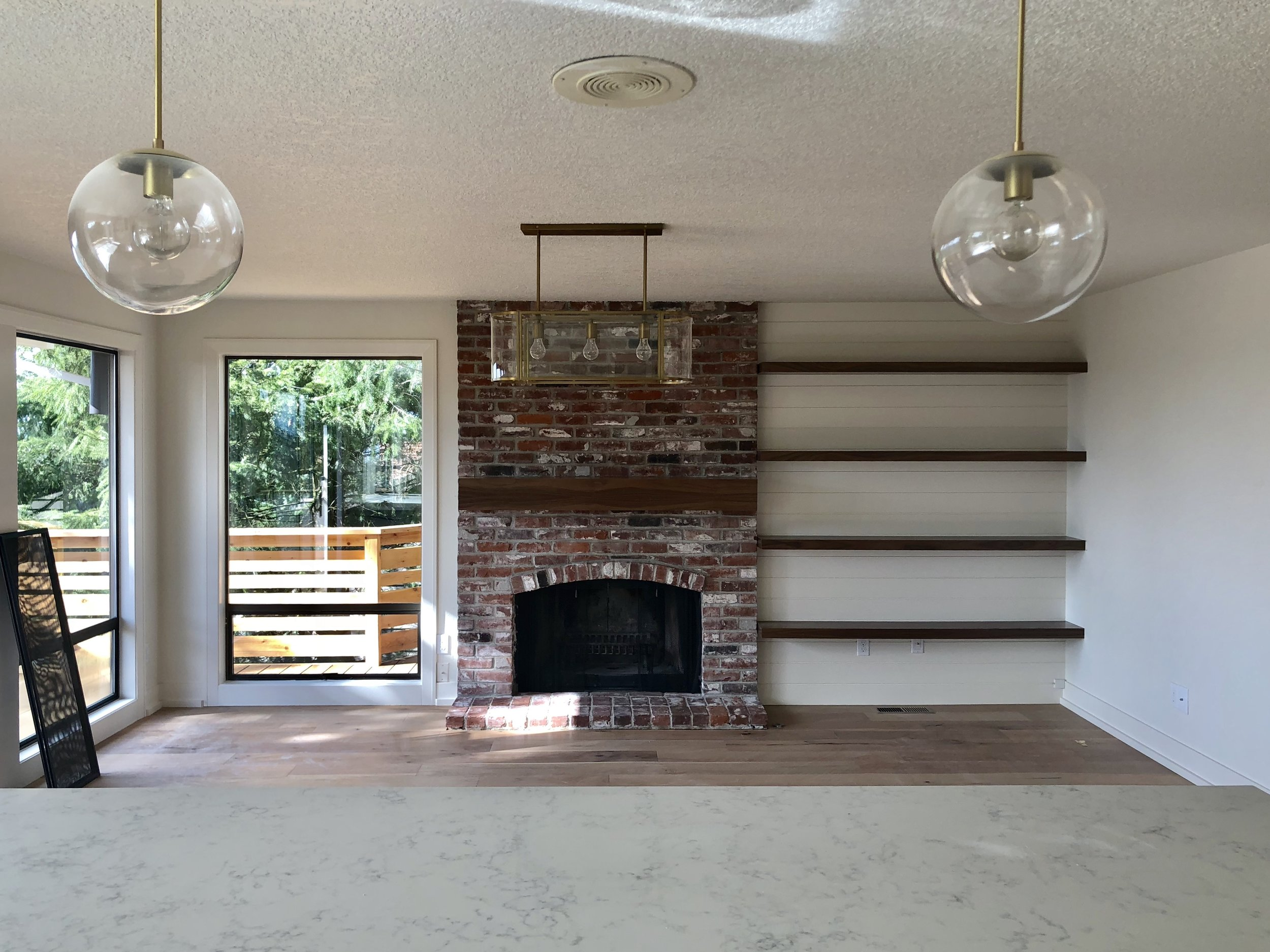 AFTER // new light fixtures, shiplap wall with floating shelves, new floors, painted fireplace