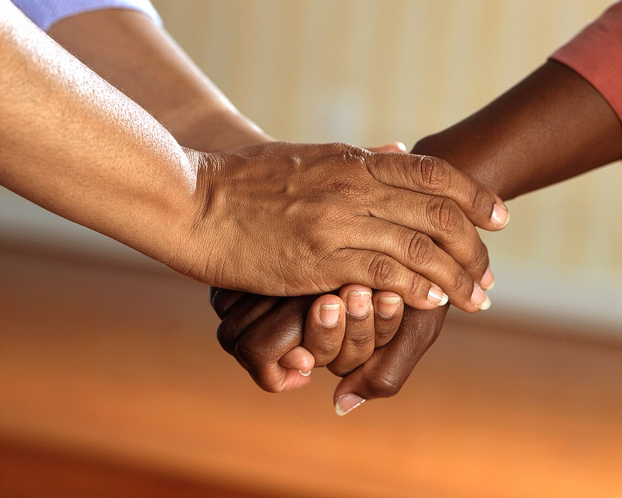 image of one person hold anothers hands representing support