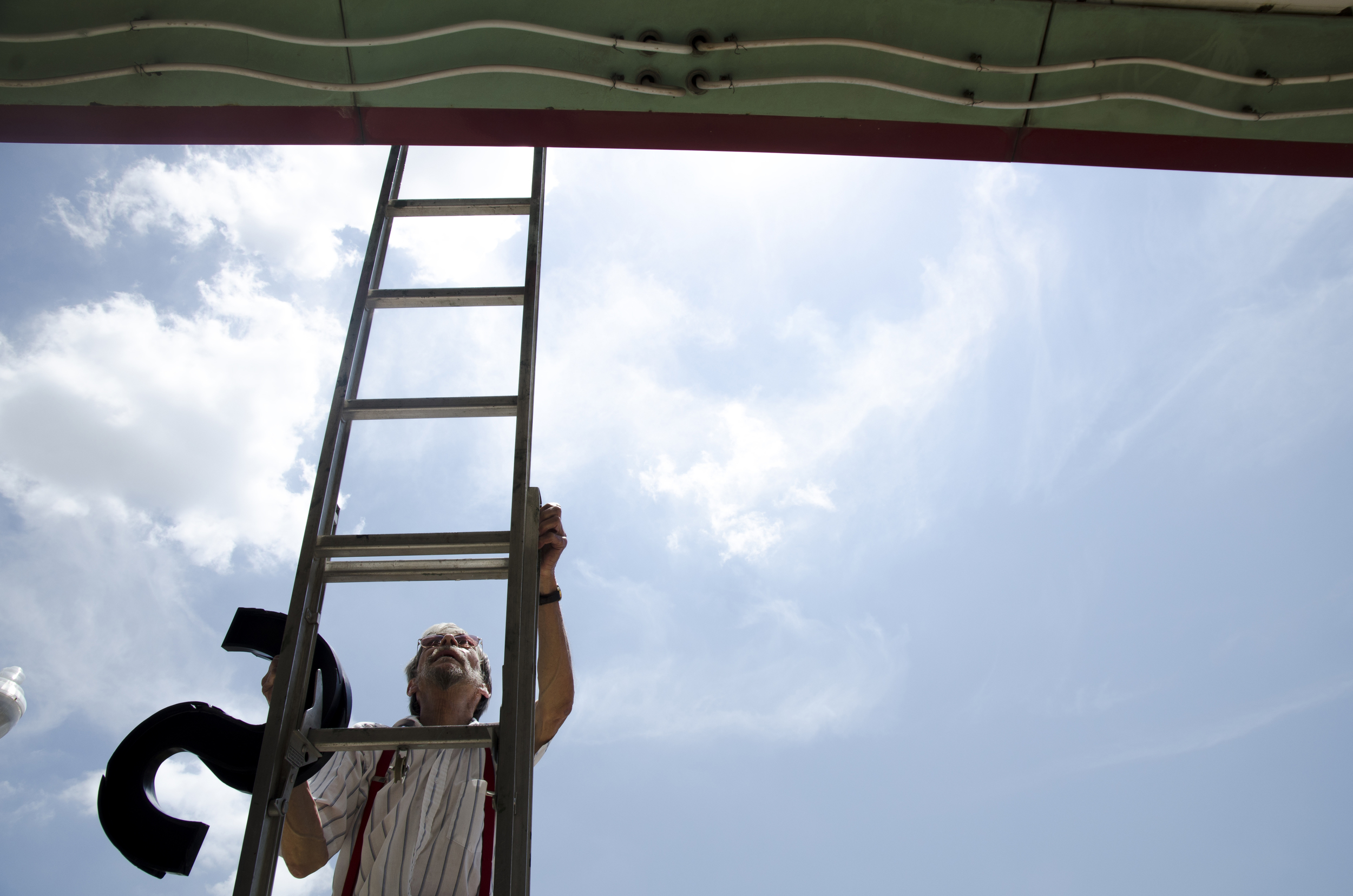 Dennis Welch, the custodian for Campus Theatre, climbs a ladder to change the marquee in Denton, Texas.