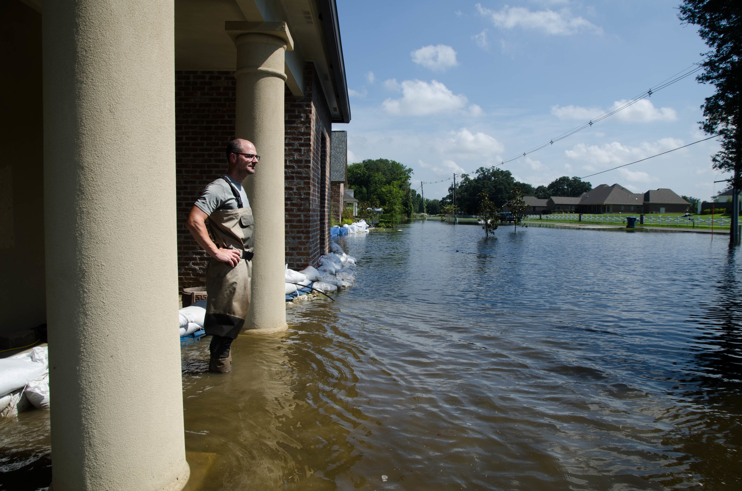 Nicholar Gros stands on his front porch, looking out on his flooded Baton Rouge neighborhood.
