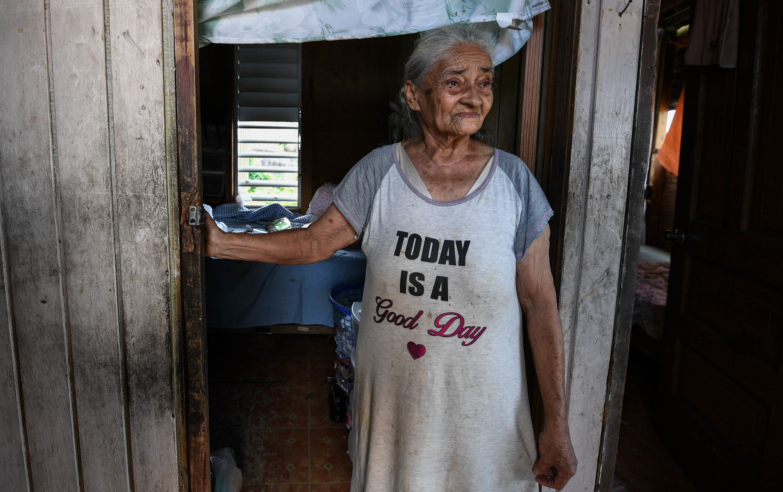 "Paola Ortiz, 84, has been alone for three months, wearing the single item of clothing she has left, a T-shirt that says, ""Today is a good day."" In the mountain village Moca with no car, she has not yet received aid. ""I've always been poor,"" said Ortiz, ""but I knew I would survive. Now, I am not sure."" After high winds took her house's walls, she rebuilt it with what was available, plywood and blue tarp. ""I have tarp, but the water still gets in; it rains on me every day."" Without power, Ortiz is unable to fill out the online form that alerts FEMA that she needs aid. Ortiz wants the world to know, ""The Puerto Ricans in the mountains are still here; tell them we need help."""