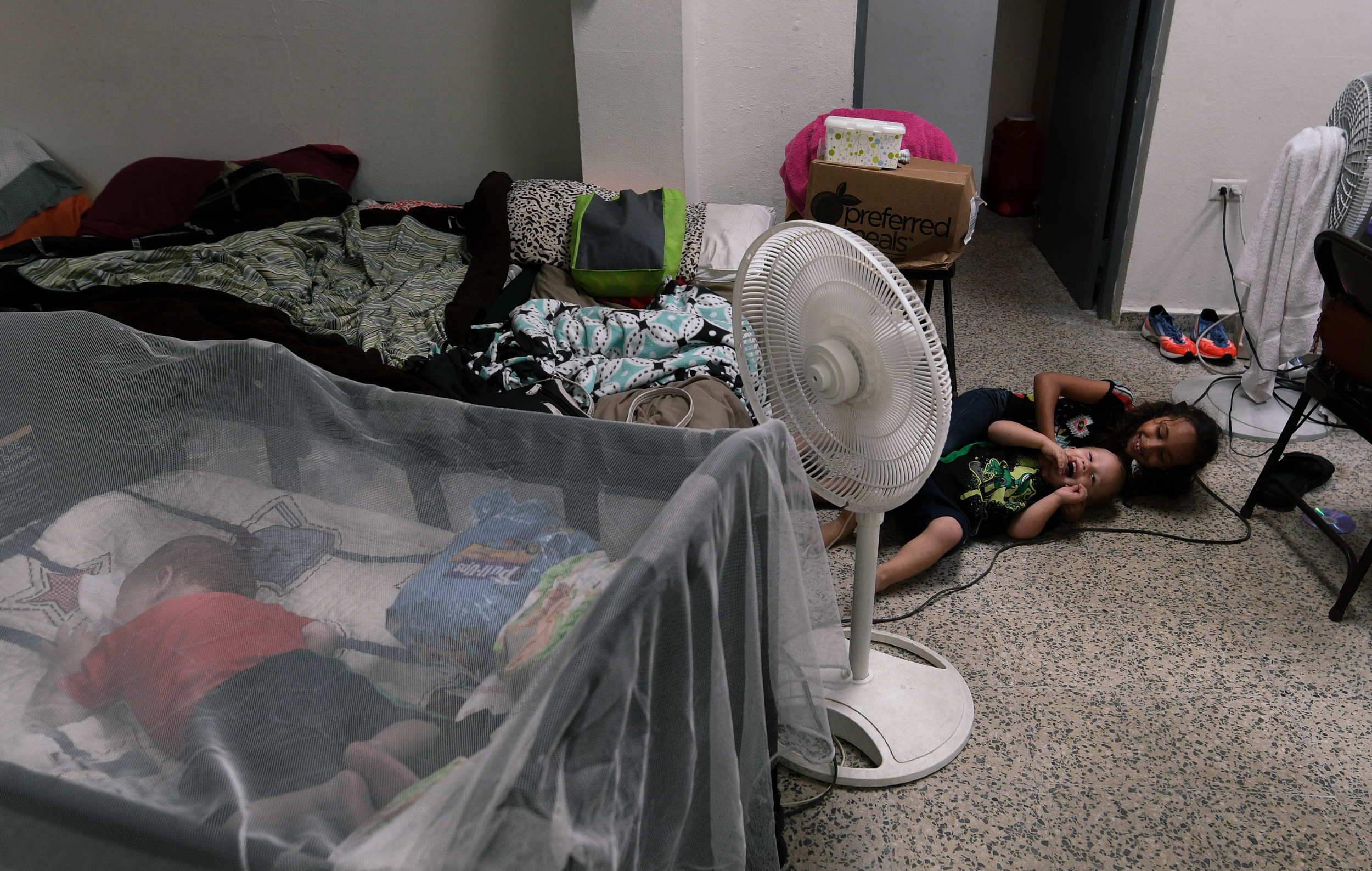 EXPAND   Four-month-old Kaleb Hernandez sleeps while his brother Mark plays with another child in the shelter. With the shelter running on a generator, a fan must be kept on the younger children so they don't overheat.
