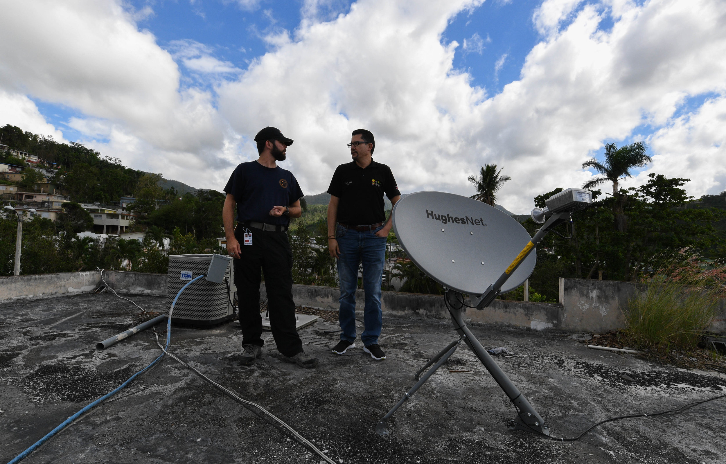 EXPAND   Darrick Kouns, a volunteer with Dallas-based nonprofit Information Technology Disaster Resource Center, discusses with Luis Seda, the network administrator for the mayor's office in the mountain village Jayuya, how they can supply communications for the local shelter. ITDRC deploys volunteers from all over the world to provide communities affected by disasters with resources to recover their IT infrastructure. Providing internet access and phones helps families reconnect when separated and aids businesses in reopening.