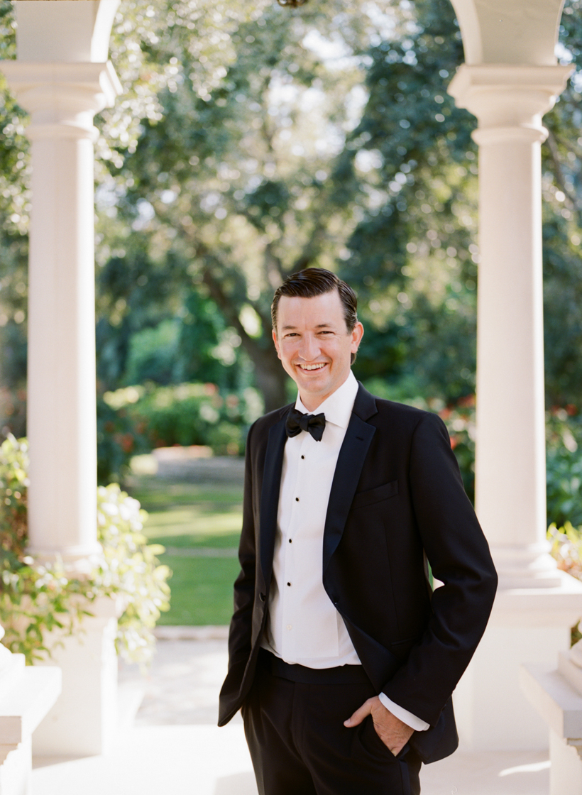Happy groom in elegant black tux on his wedding day in Palm Beach - photo by Kat Braman