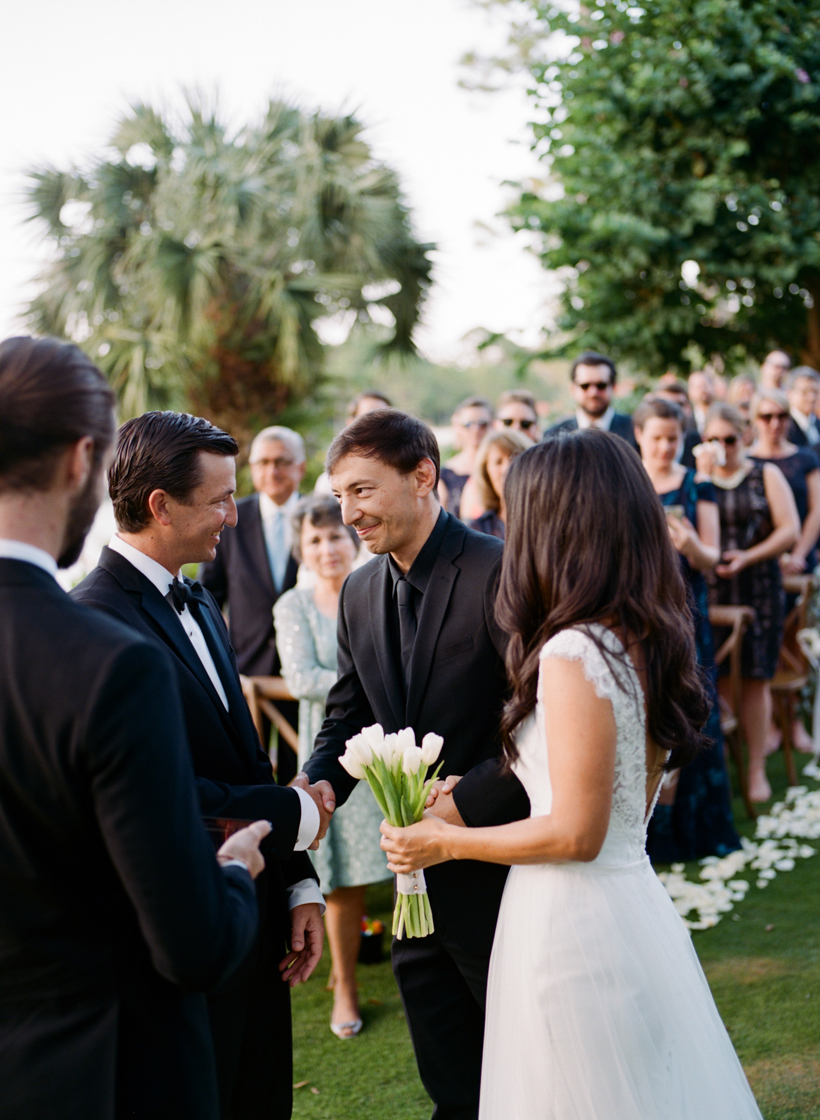 Bride being given away by her brother as their mom looks on in this beautiful garden wedding.  Photo by Kat Braman