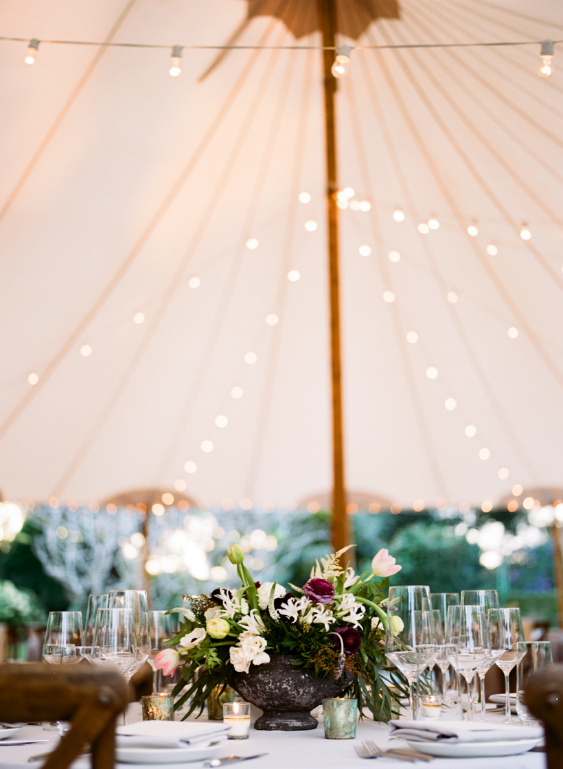 Wedding reception tables with florals by Port and Palm Co. set in a Sperry Tent.  Photo by Kat Braman