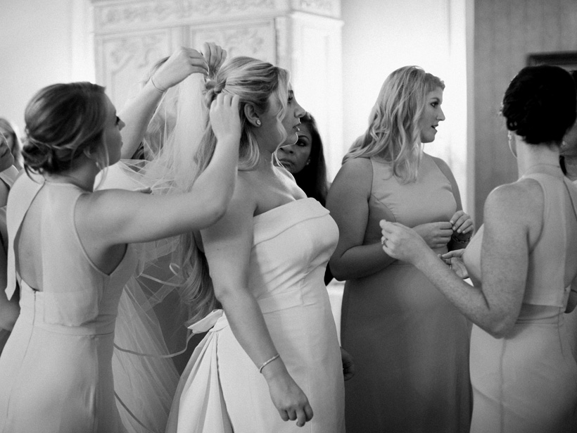 The bridesmaids help the bride put on her veil after she is dressed in her gorgeous Carolina Herrera wedding dress. Photo by Kat Braman