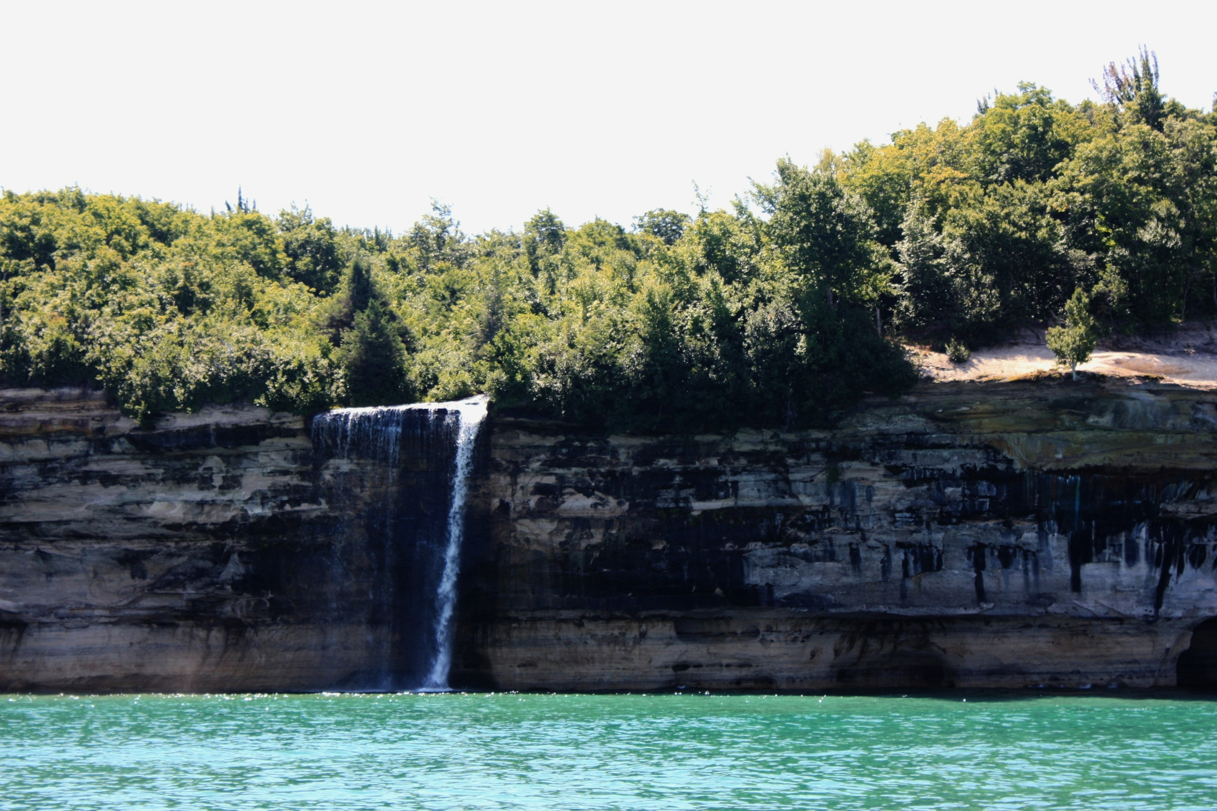 """There are  a few waterfalls  along Pictured Rocks National Lakeshore that constantly quench Lake Superior's thirst, including this little fella, Spray Falls, which is best viewed by boat. Fun fact: the remains of a ship named """"Superior,"""" which sank in 1856, lie at the base of Spray Falls in about 20 feet of water."""
