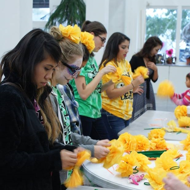 Volunteers assist visitors making paper marigolds during Denton's Day of the Dead Festival at the Arts Center.
