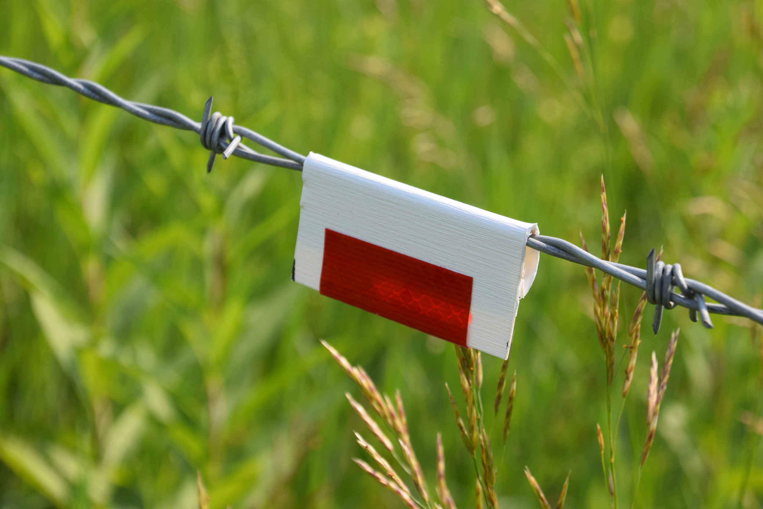 Simple reflectors on fences can increase visibility for wildlife.