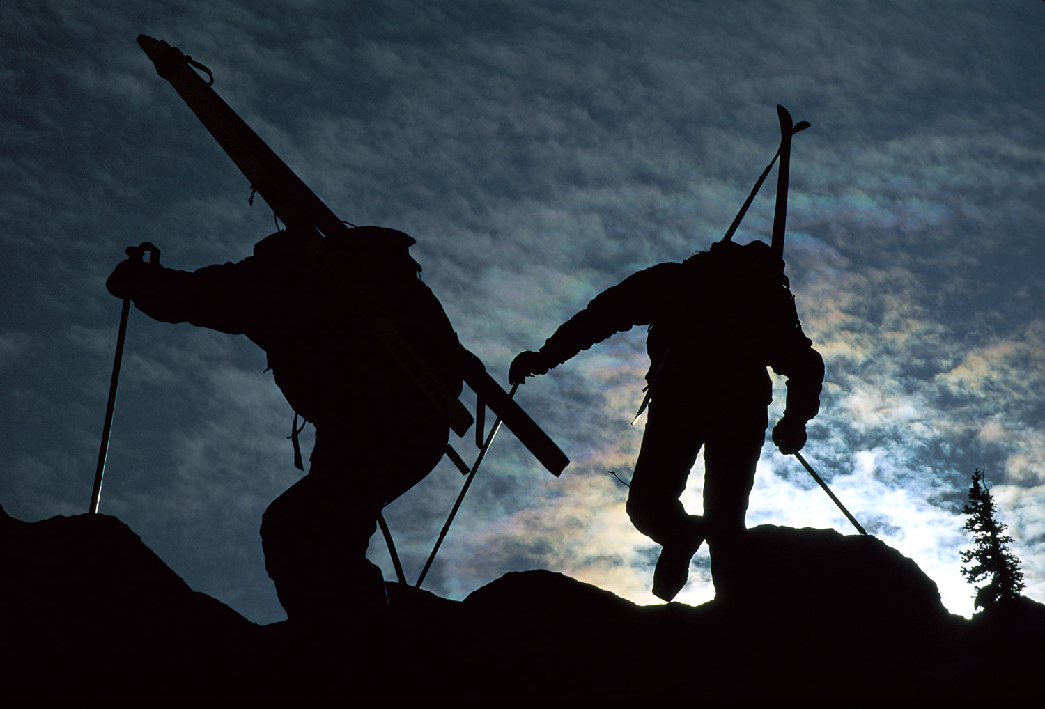 """Between Rock and Sky"", Silhouetted Backcountry Skiers climb for"