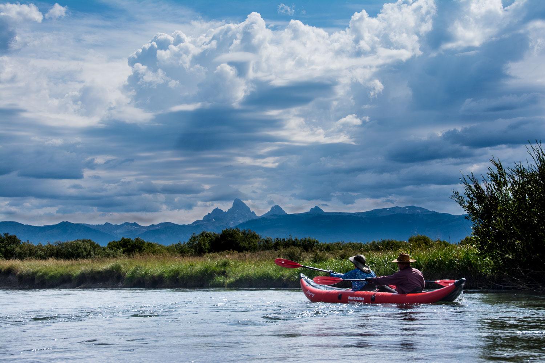A couple leisurely paddling their kayak on the Teton River, near
