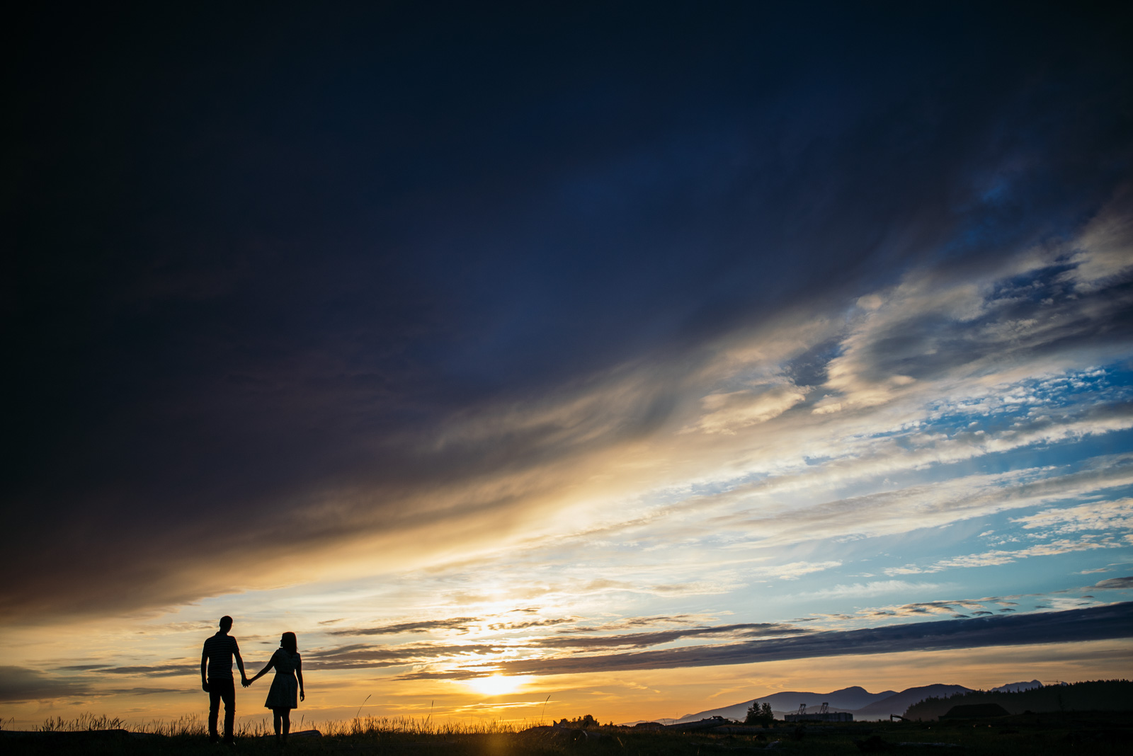 ^I mentioned it above, but I'll say it again…I'm a sucker for silhouettes! During Aaron and Ramiza's engagement shoot at Iona Beach, we were gifted with just a ridiculous sunset with awesome dark clouds and bright colours. I asked them to walk up onto the grassy ridge and watch the sunset, and this was the resulting photo.